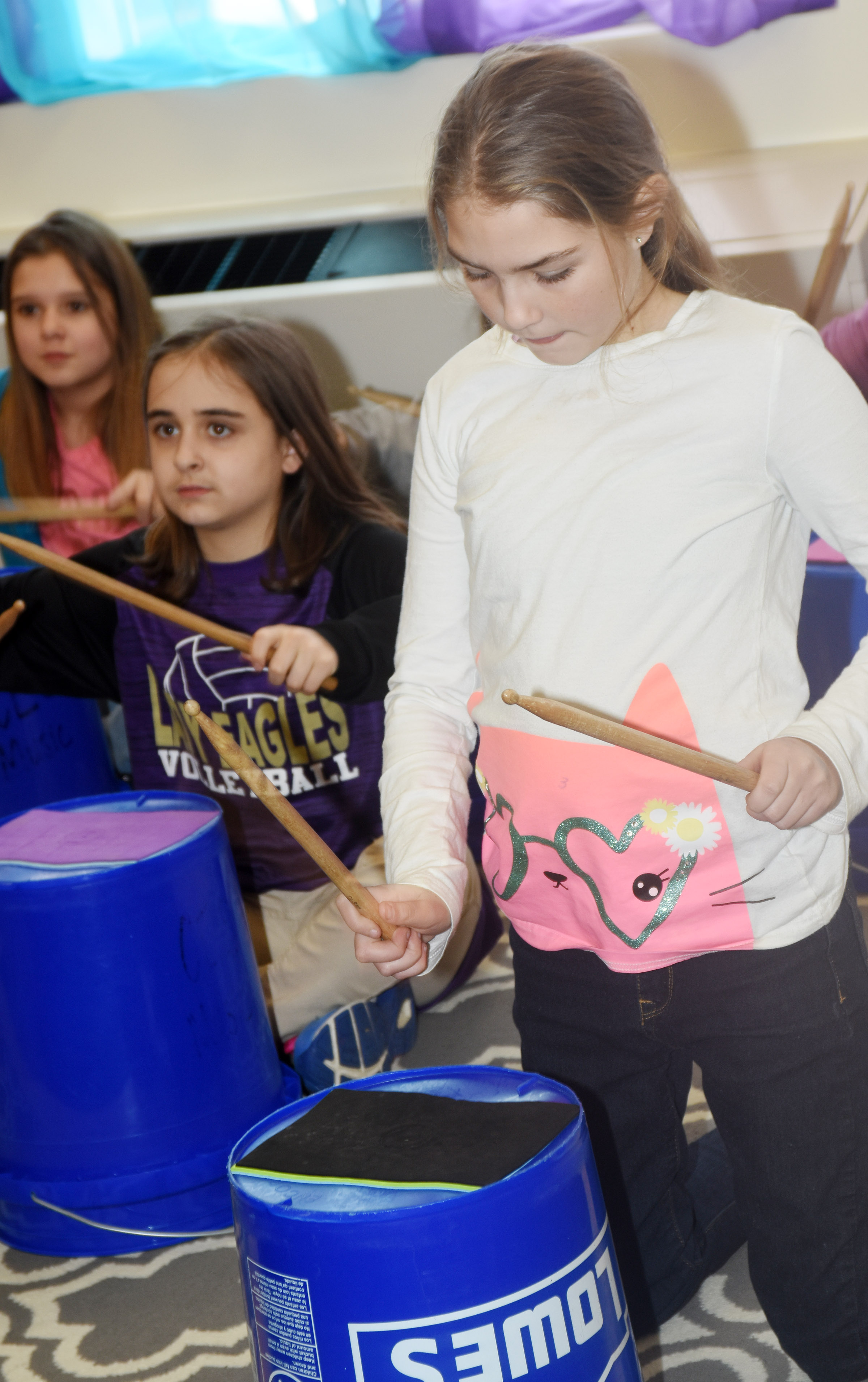 CES fifth-grader Harley Couch-Allen plays the bucket drums.