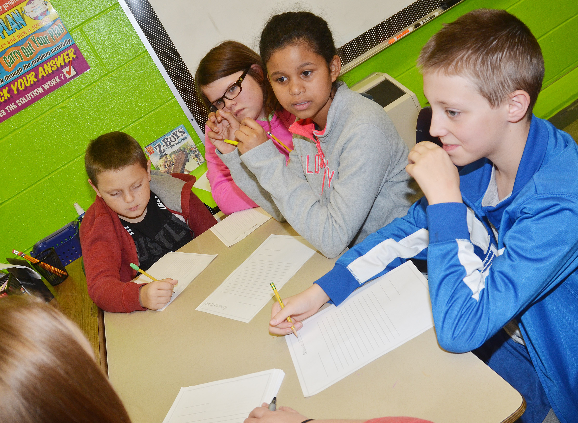 Campbellsville University student teacher Melissa Langstaff discusses how to correctly write the parts of a letter with, from left, CES fifth-graders Ethan Marrs, Keeley Dicken, Destiny Bradley and Jaxon Garrett.