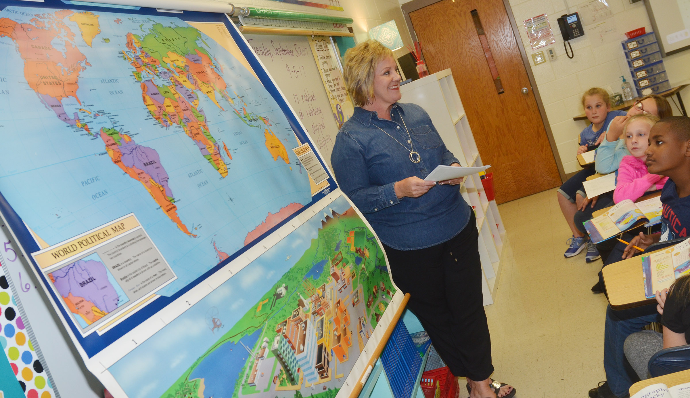 CES fourth-grade teacher Kaye Agathen talks to her students about where to find Kentucky on a world map.