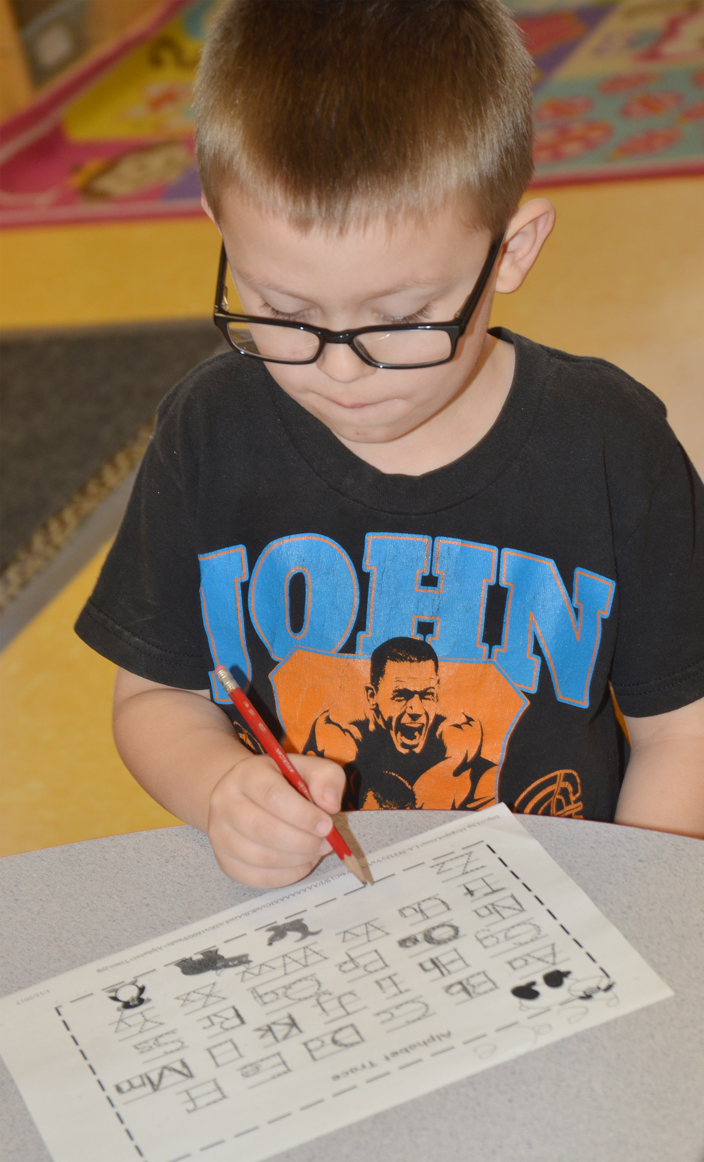 CES preschool student Reece Williams practices writing the alphabet.