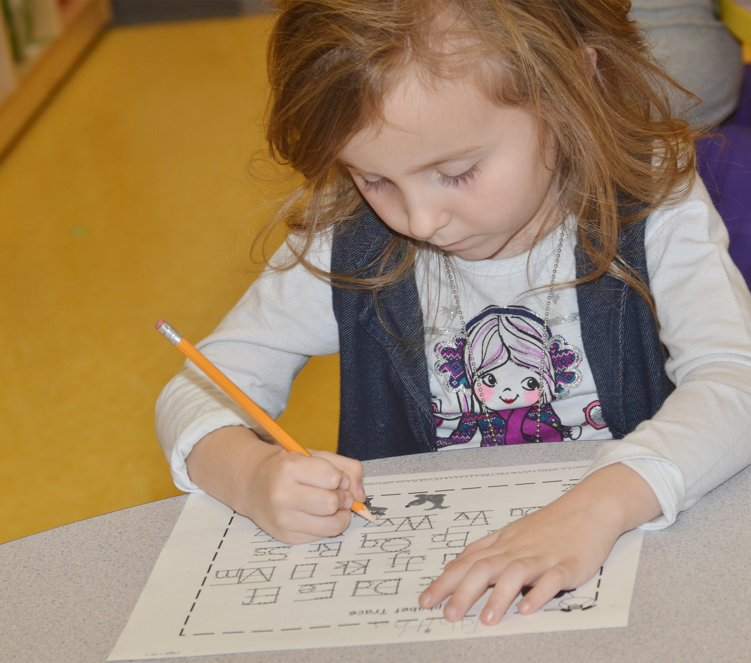 CES preschool student Tabitha Leggett practices writing the alphabet.