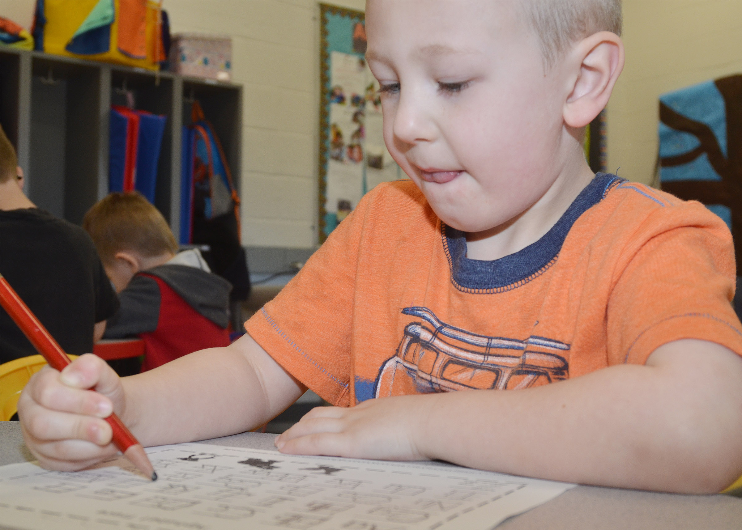 CES preschool student Cameron Dean practices writing the alphabet.