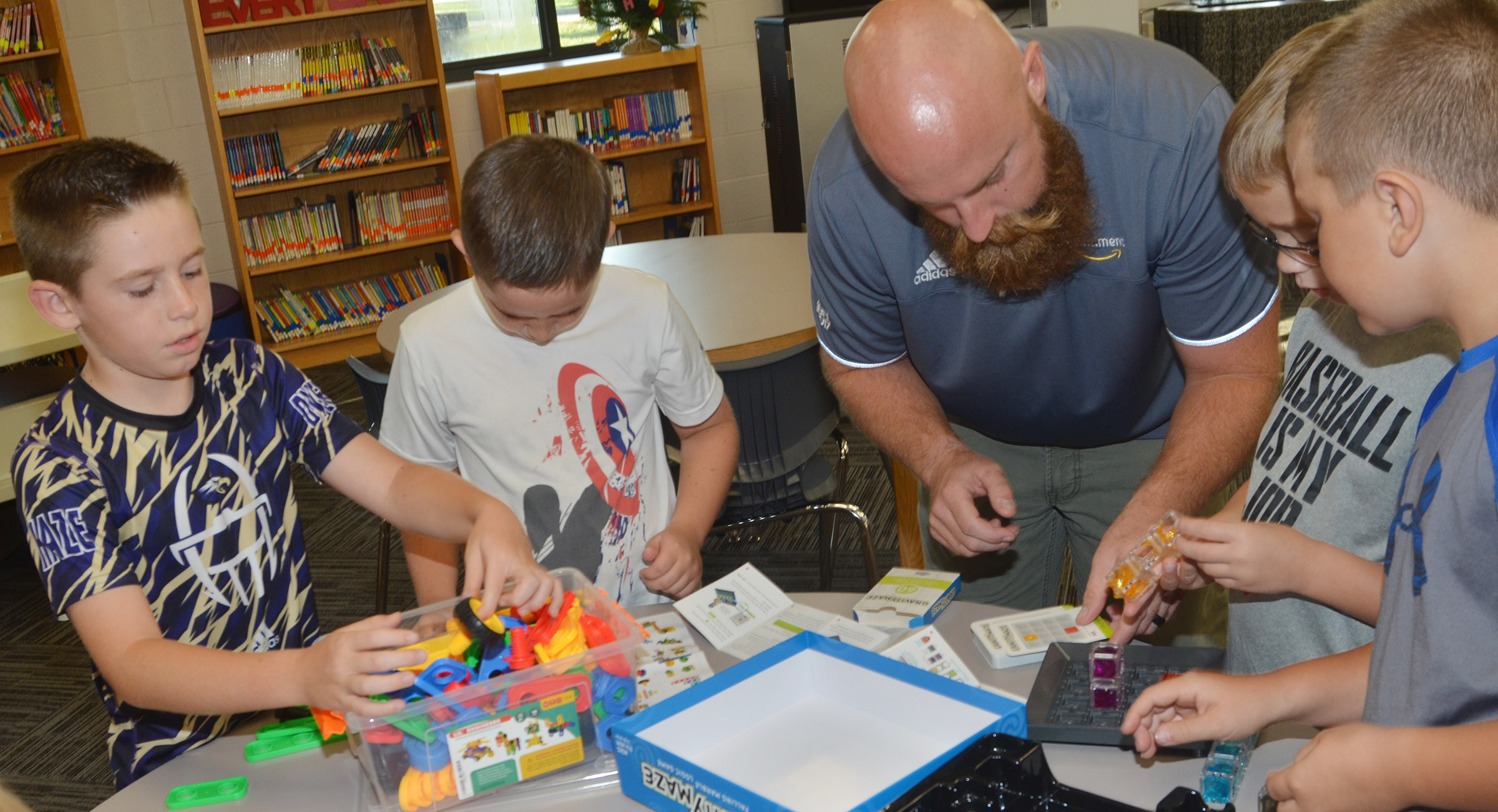 Chad Forsyth, an operations manager at Amazon, plays with STEM toys with, from left, third-graders Lanigan Price and Luke Adkins, fourth-grader Cameron Estes and third-grader Cayton Lawhorn.
