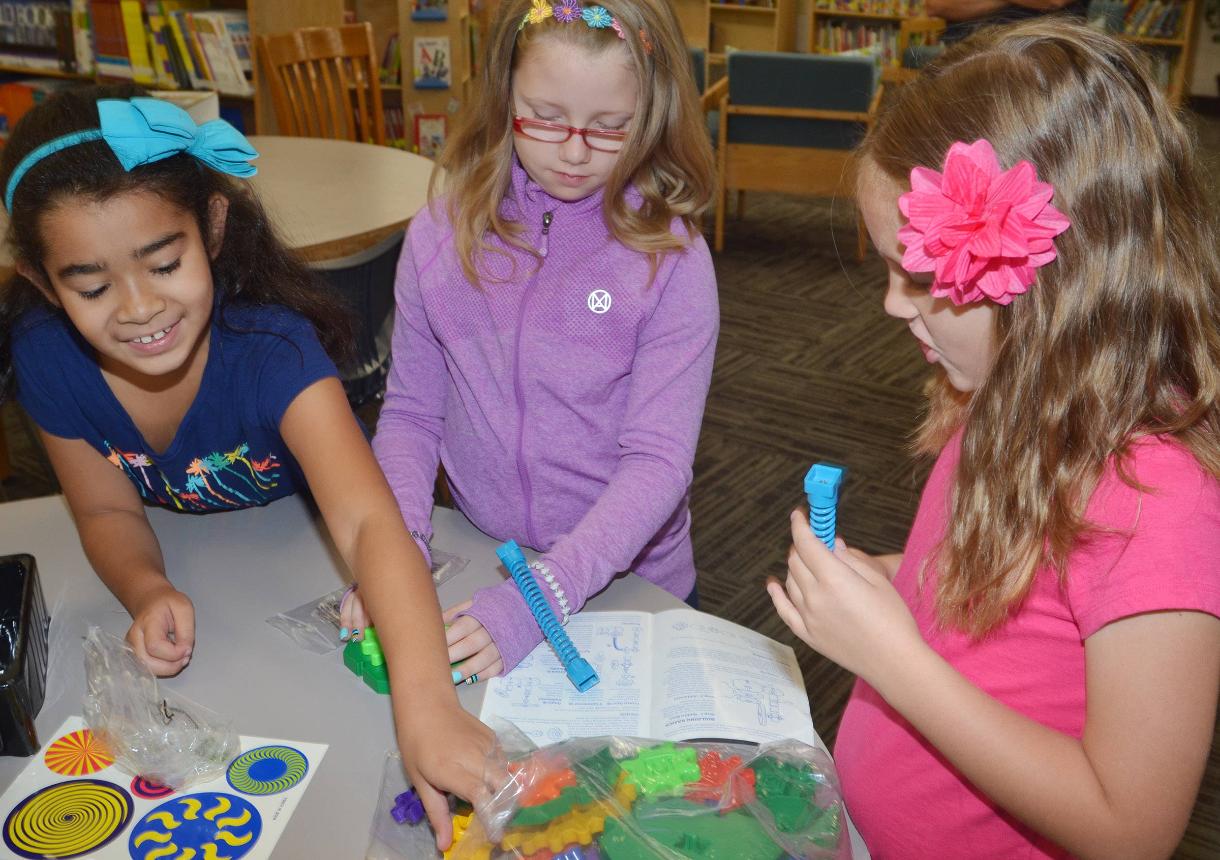 CES third-grader Sophia Santos, at left, and fourth-graders Gracie Pendleton and Madisyn Bradfield play with STEM toys donated by Amazon.