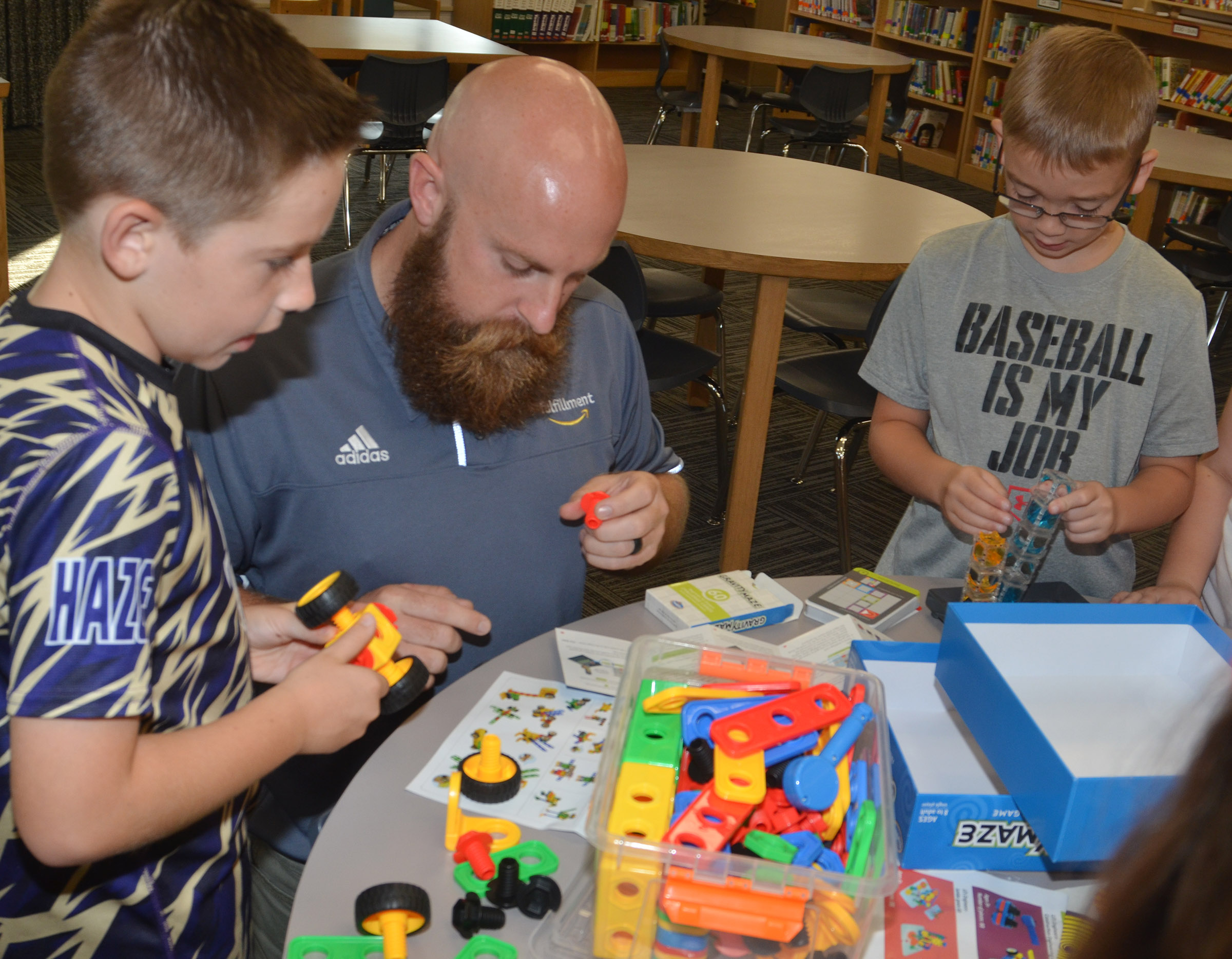 Chad Forsyth, an operations manager at Amazon, plays with STEM toys with third-grader Lanigan Price, at left, and fourth-grader Cameron Estes.