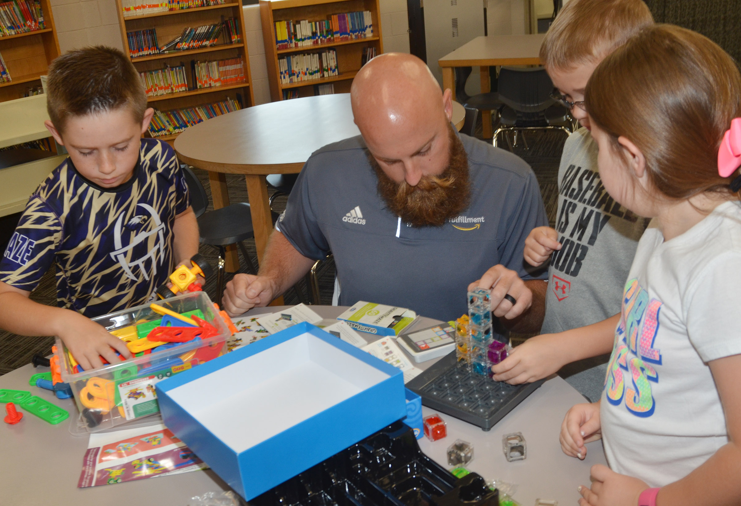 Chad Forsyth, an operations manager at Amazon, plays with STEM toys with, from left, third-grader Lanigan Price and fourth-graders Cameron Estes and Maylee Wilds.
