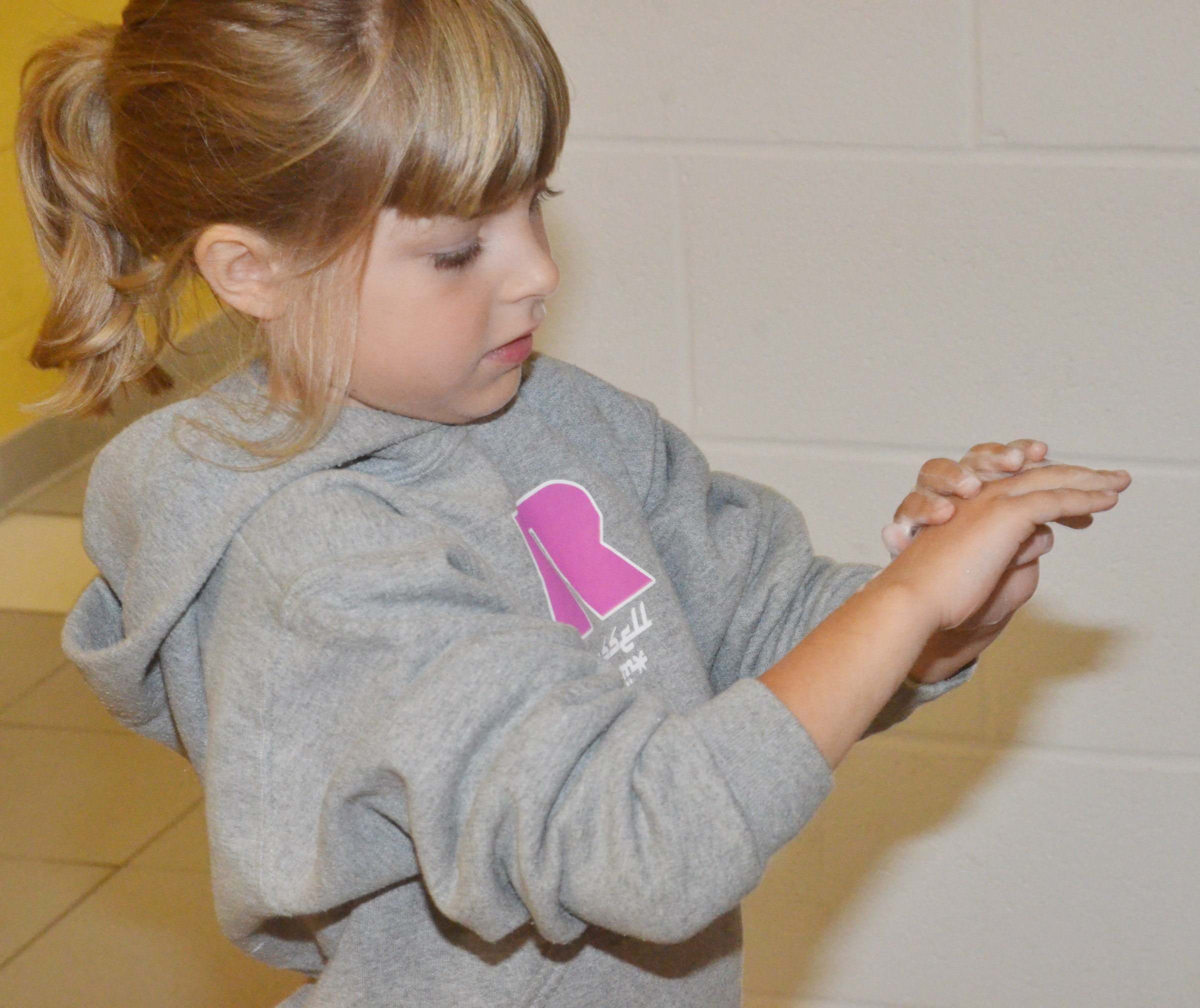 CES first-grader Madison Wilhoite practices washing her hands.