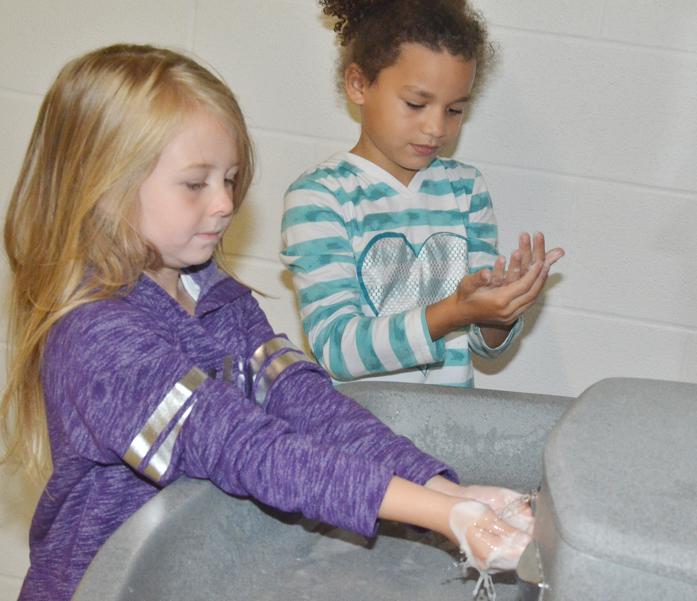 CES first-graders Jewell Brewster, at left, and Aleeya Spaulding practice washing their hands.