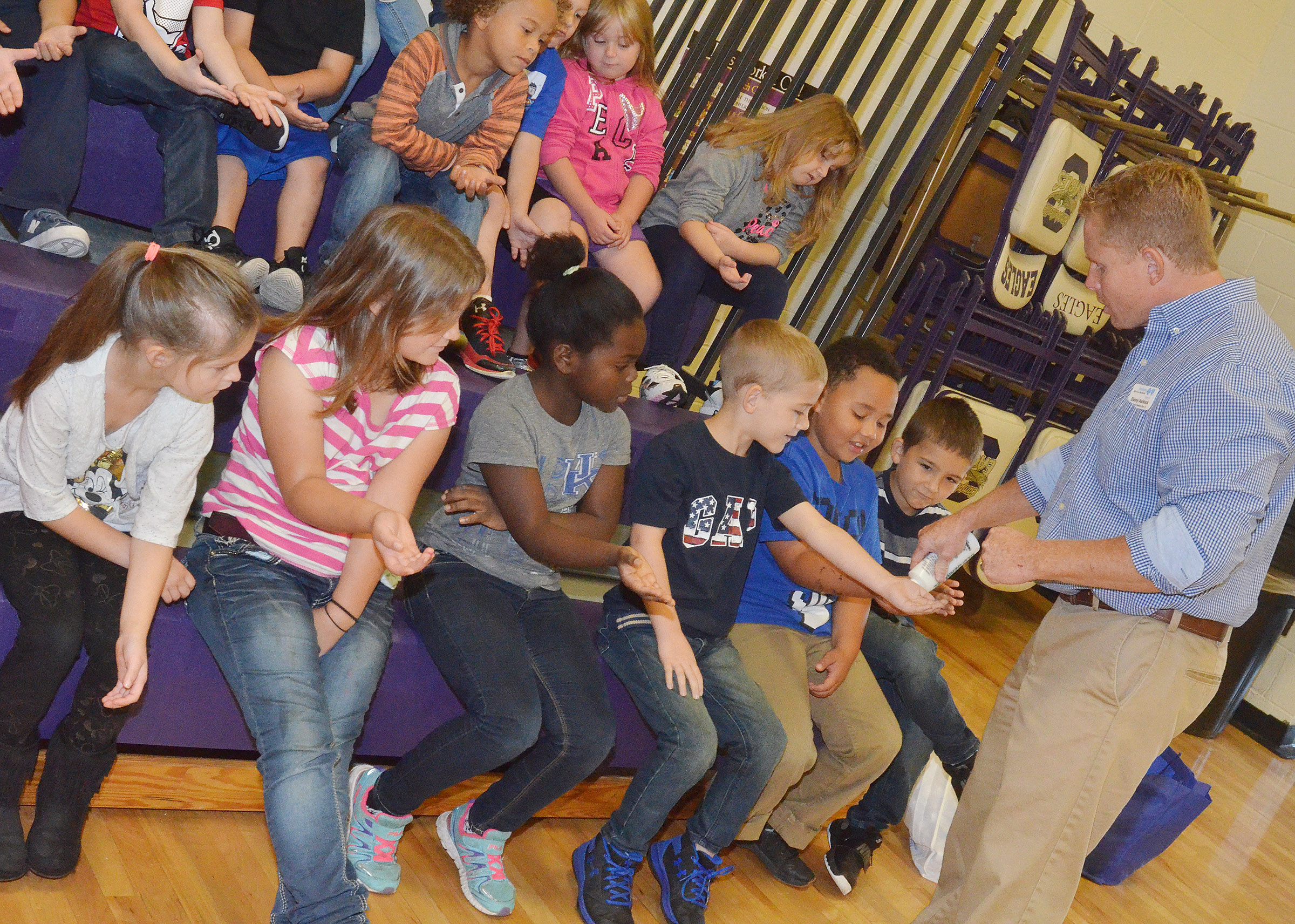 "Danny Ashlock, a representative from the Anthem insurance company, places ""germs"" in first-graders hands to see how well they can wash them away."