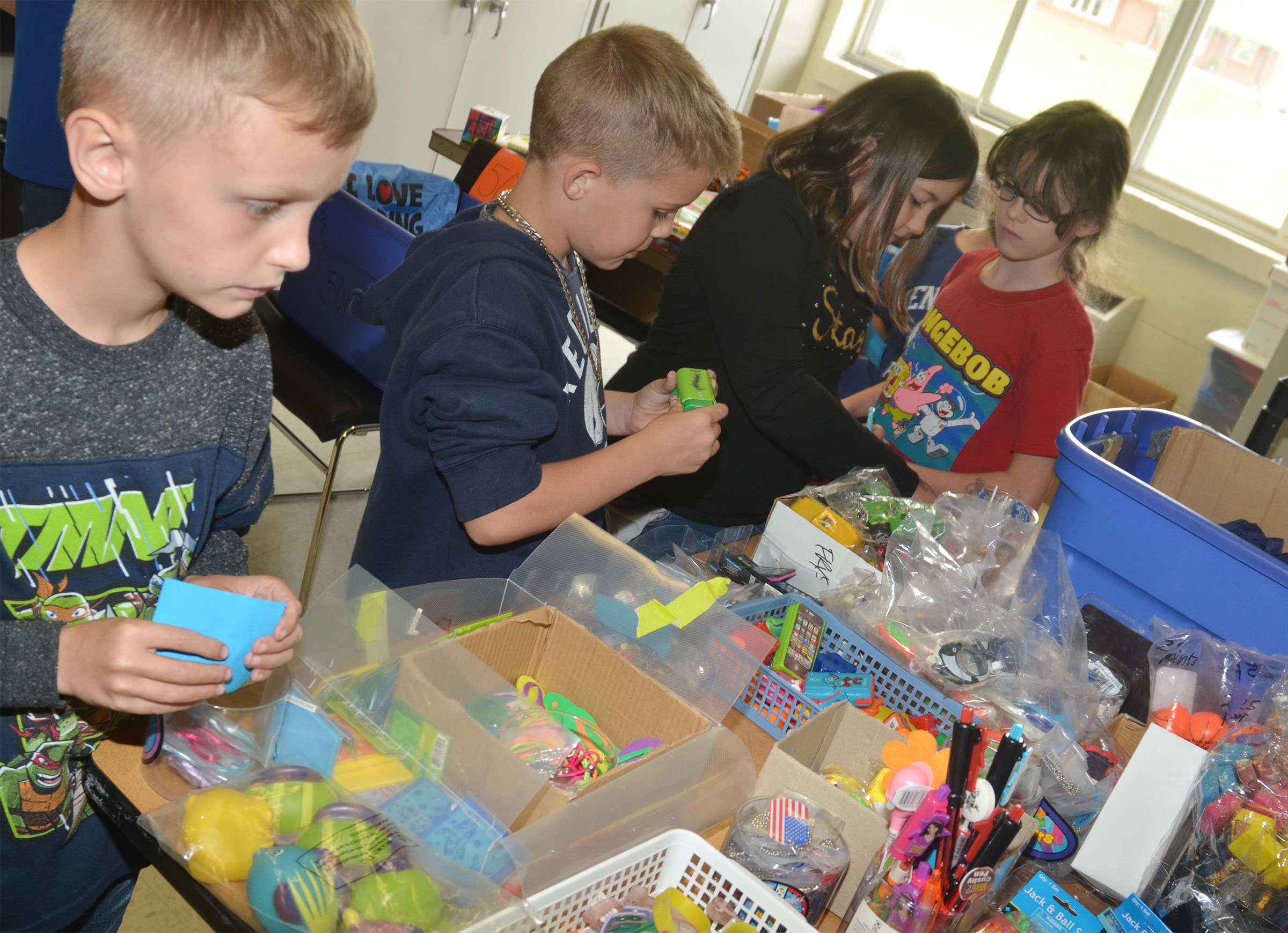 CES second-graders, from left, Aaron Ritchie, Kadin Coppage, Marissa Sumners and Lilly Wise shop with their AR points.