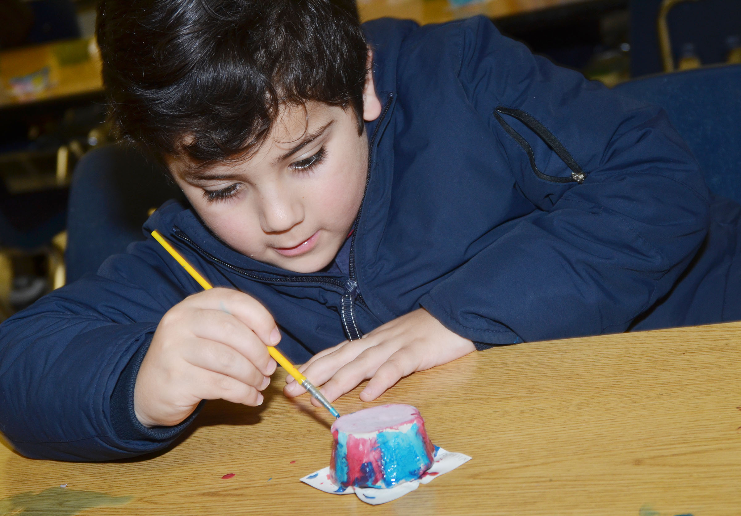 CES first-grader Nicholas Almeida paints his pot.
