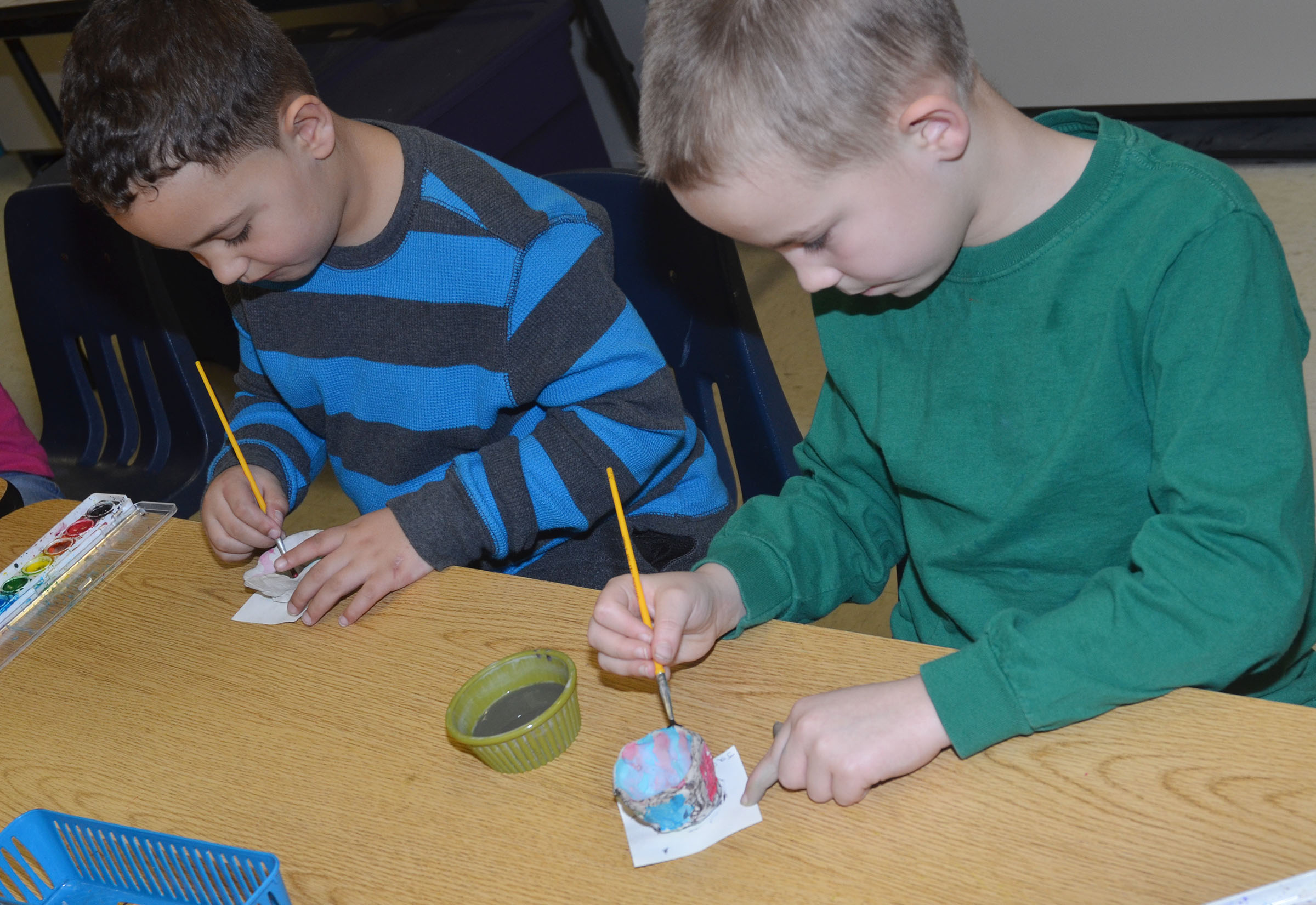CES first-graders Marion Mann, at left, and Jackson Bates paint their pots.