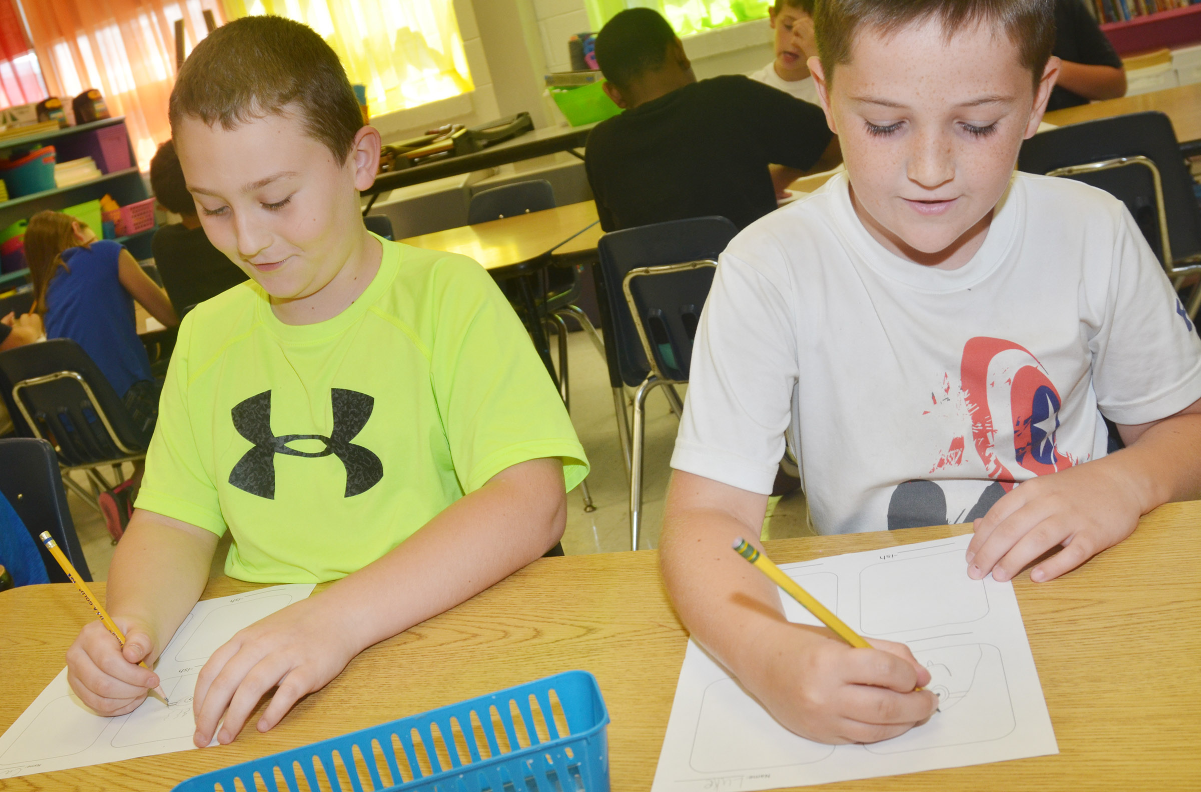 "CES third-graders Carson Ford, at left, and Luke Adkins draw their ""-ish"" drawings."