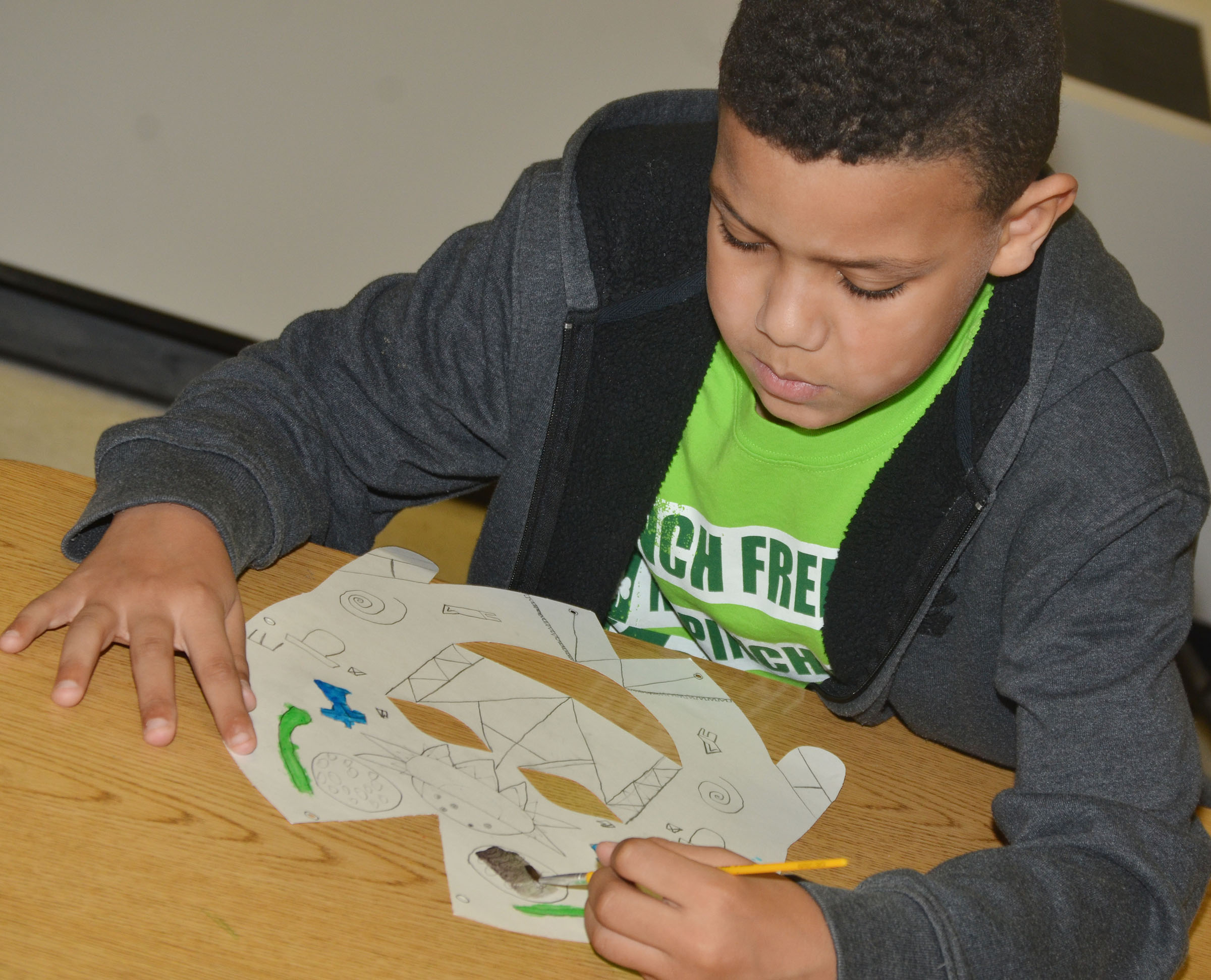 CES third-grader Christian Hart paints his African mask.