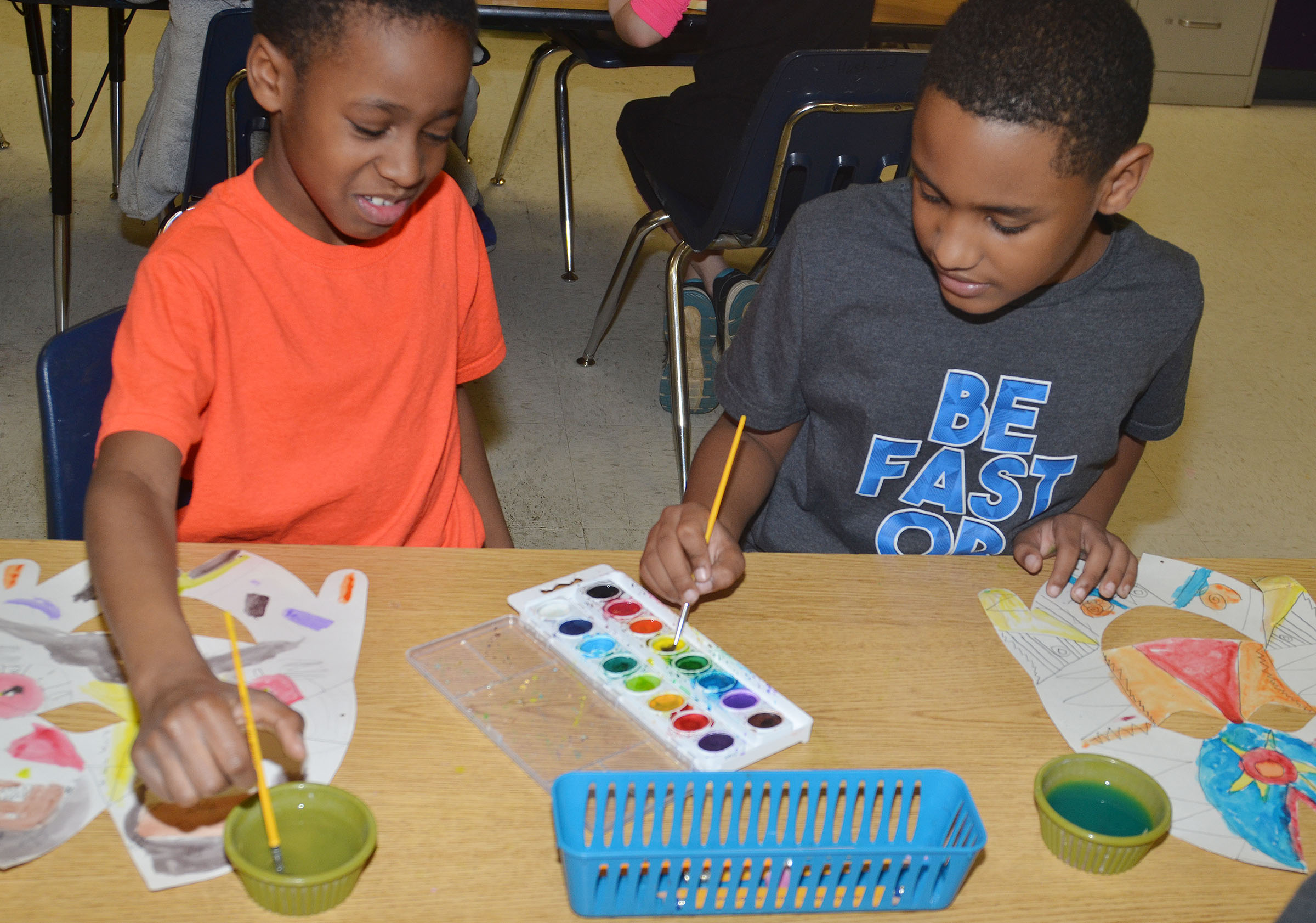 CES third-graders John Gholston, at left, and Shaiden Calhoun paint their African masks.