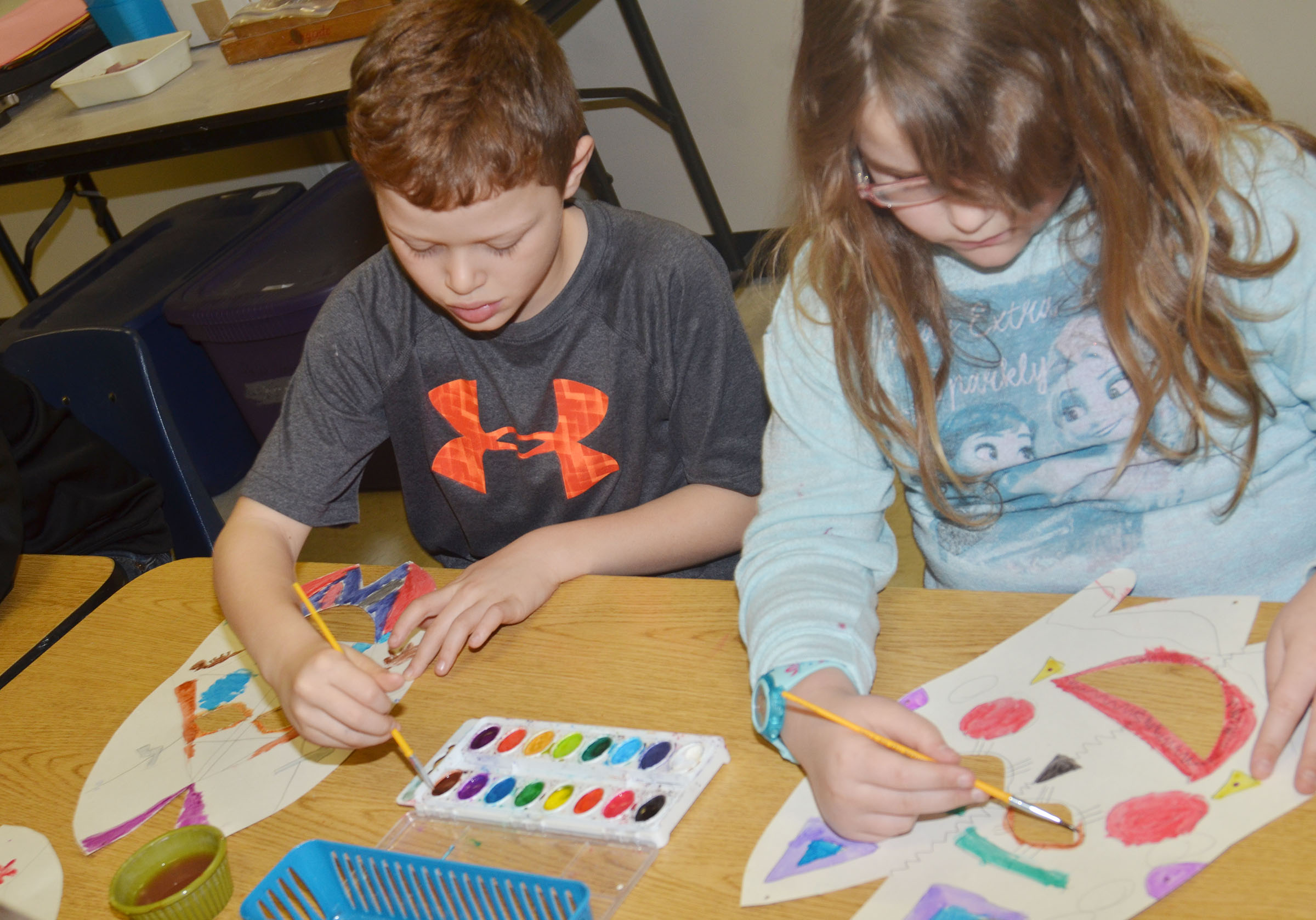 CES third-graders Demetrious Dickens, at left, and Eleana Brewer paint their African masks.