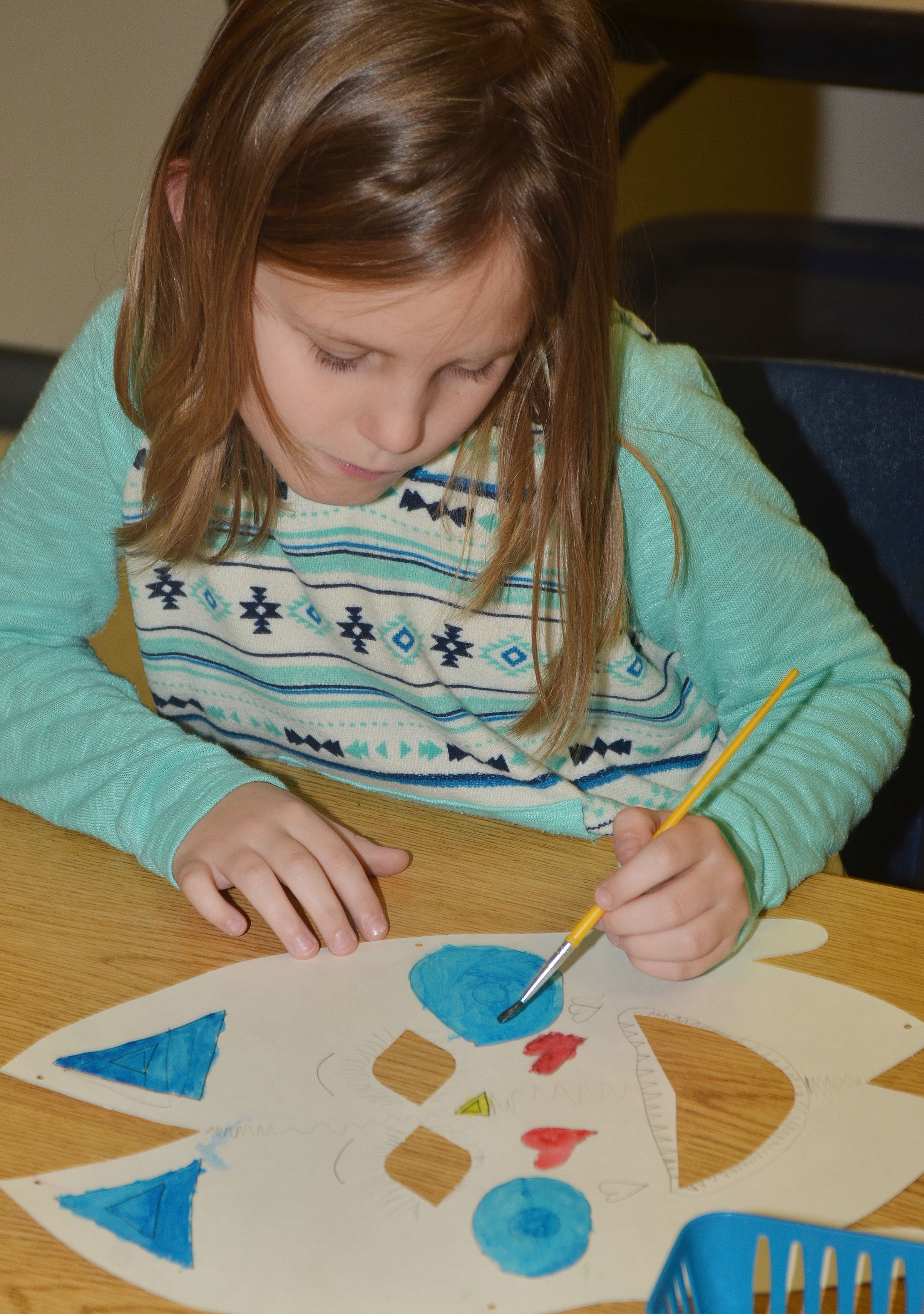 CES third-graders Madisyn Bradfield paints her African mask.