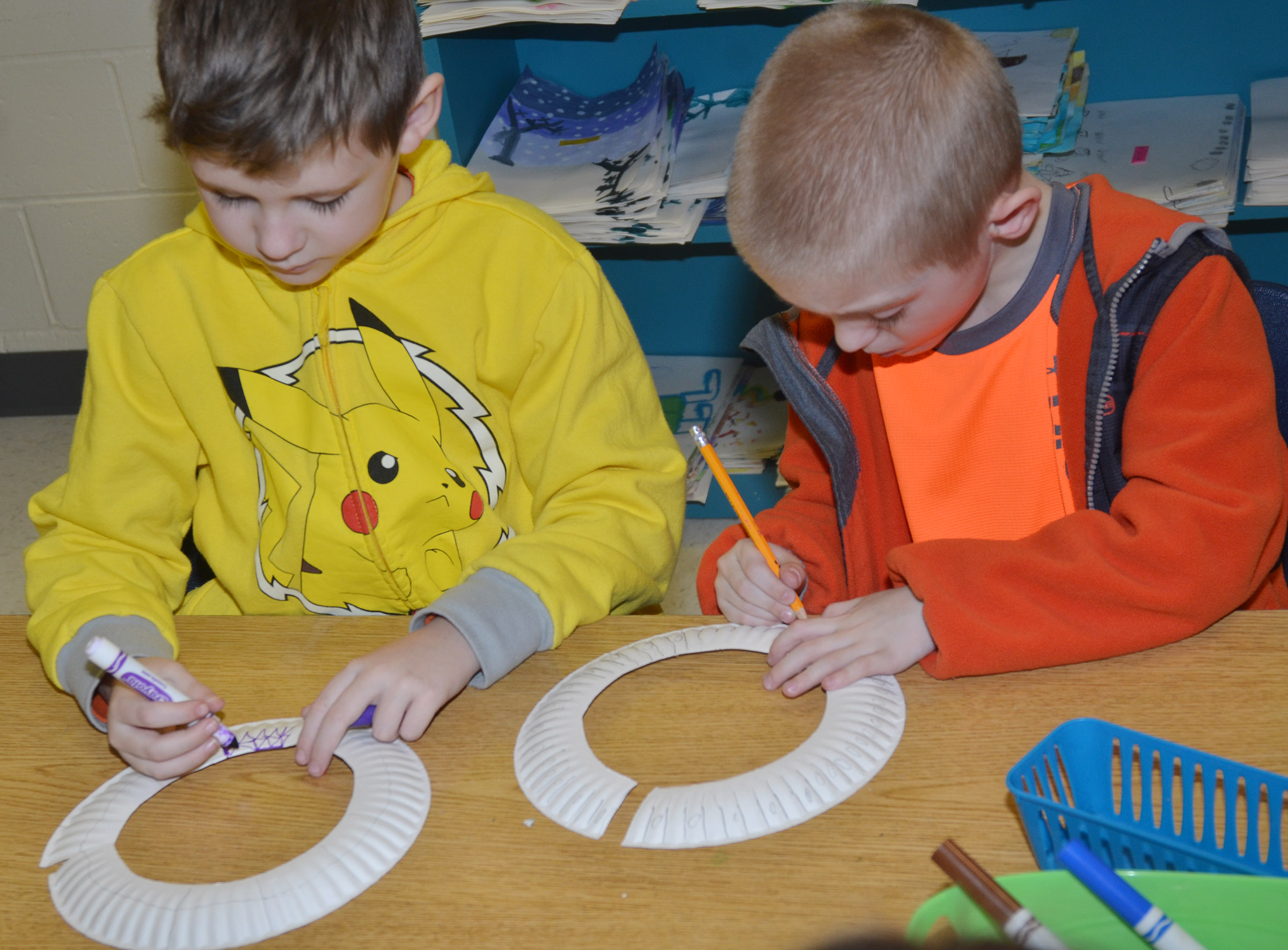 CES second-graders Ryan Tungate, at left, and Evan Cundiff draw designs on their African necklaces.