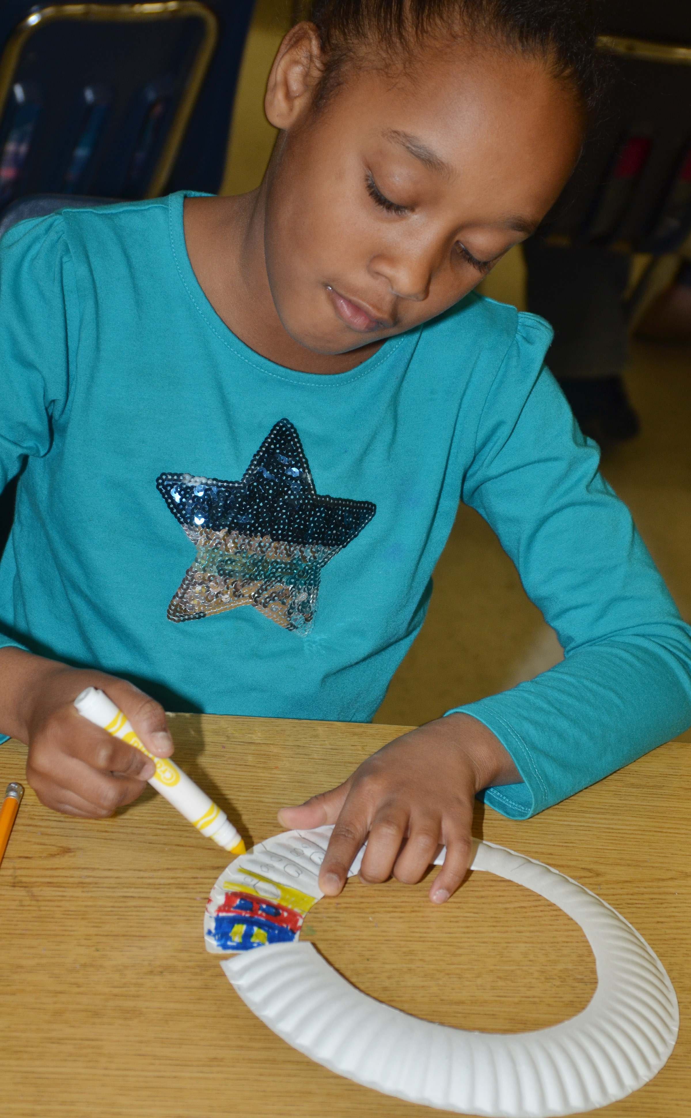 CES second-grader Lashonda Wilkinson colors her African necklaces.