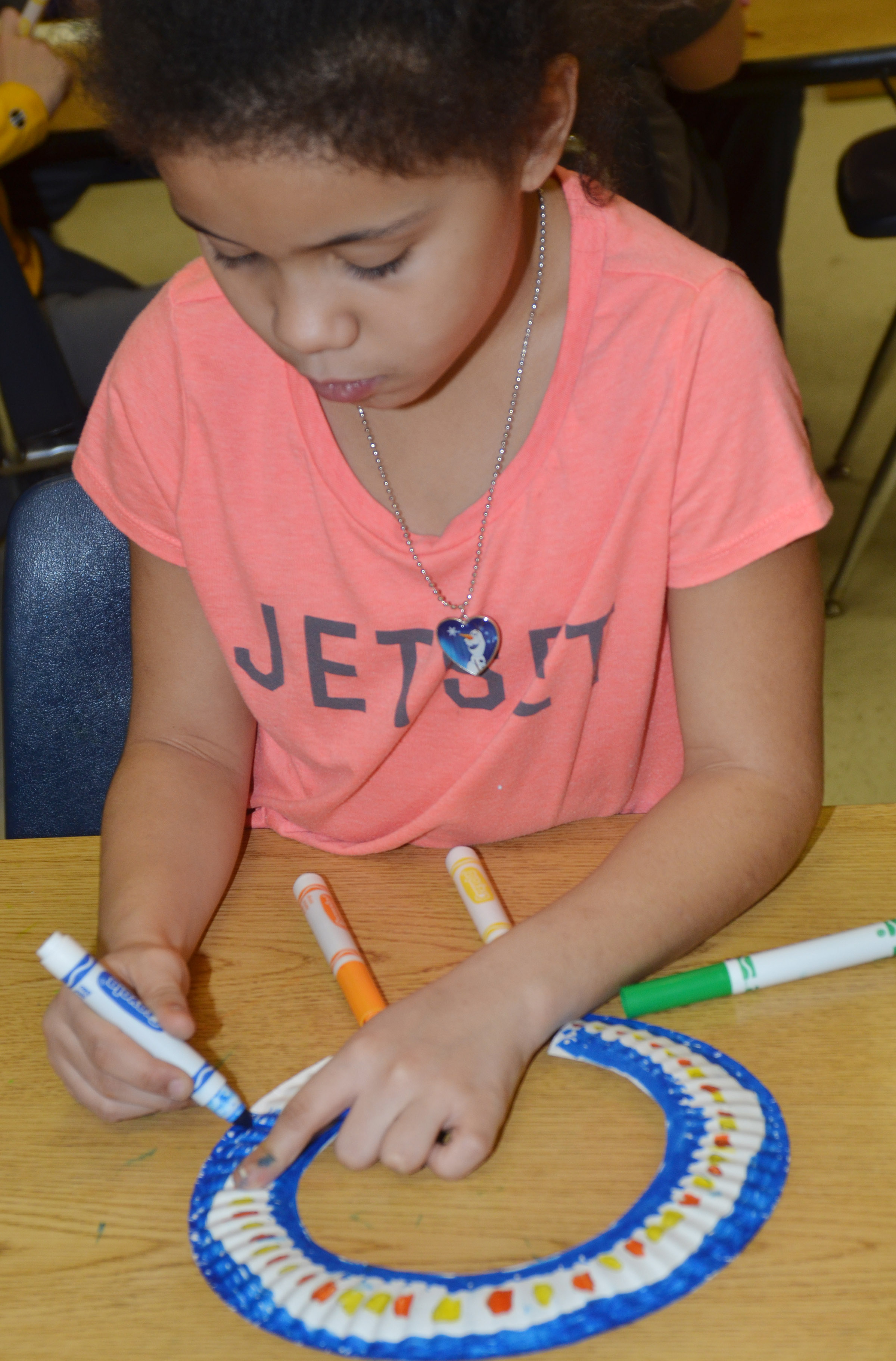 CES second-grader Alex Wilson colors designs on her African necklace.