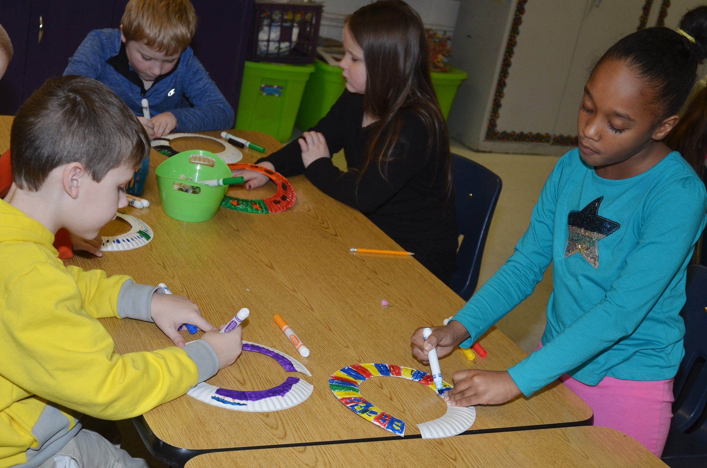 CES second-graders Ryan Tungate, at left, and Lashonda Wilkinson color designs on their African necklaces.