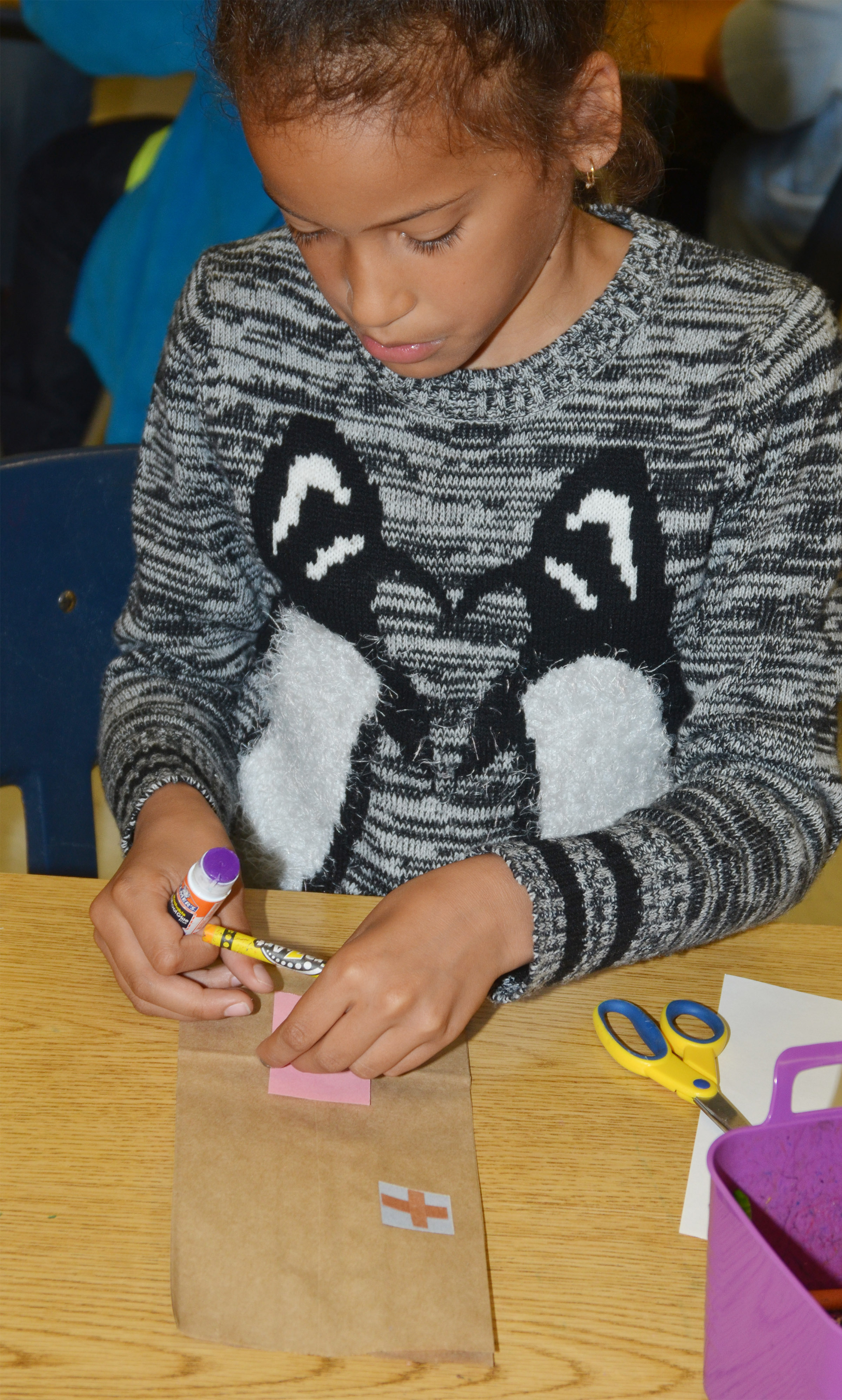 CES second-grader Yazlyn Sutton makes her paper building.