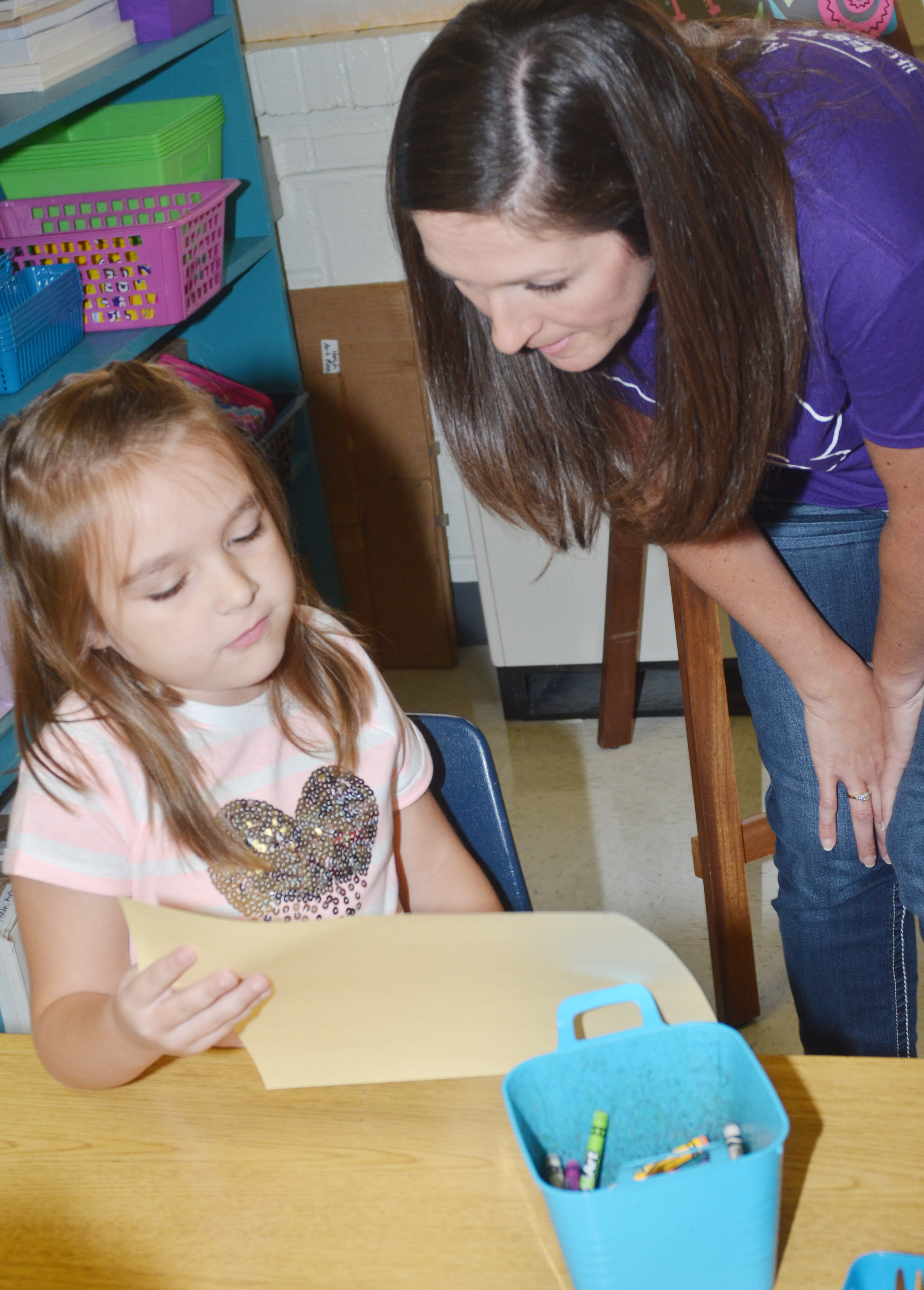 "CES first-grader Aubrey Allen shows art teacher Adrienne Hash her ""Beautiful Oops"" artwork."