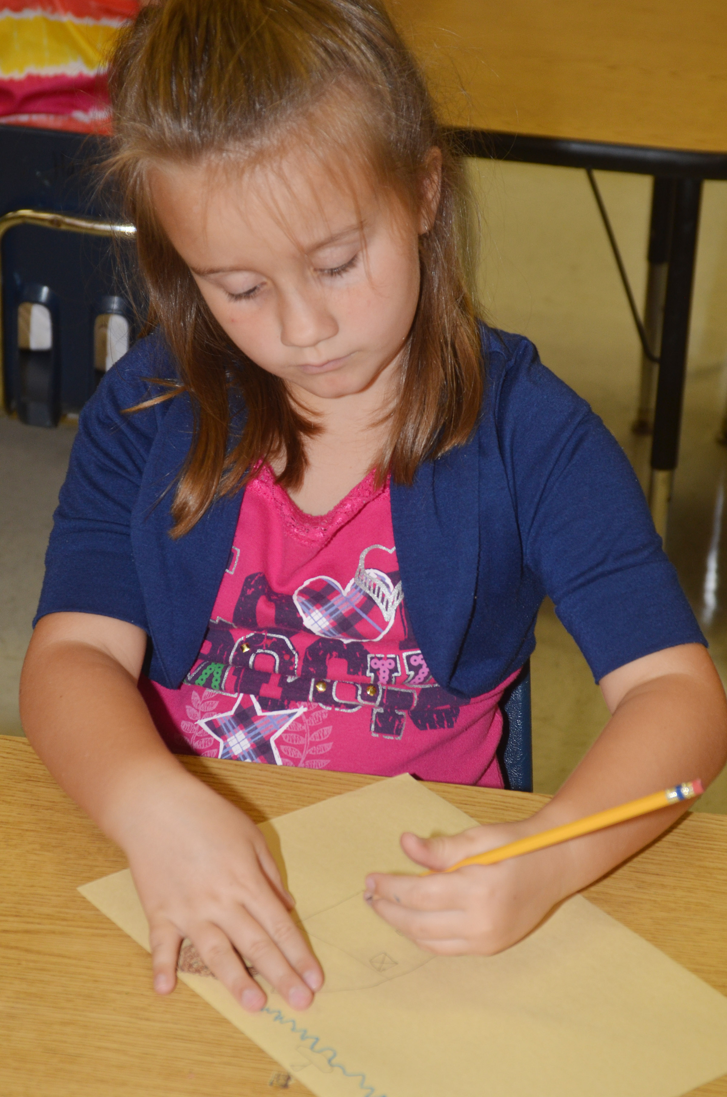 "CES first-grader Natalee Shaw draws her ""Beautiful Oops"" artwork."