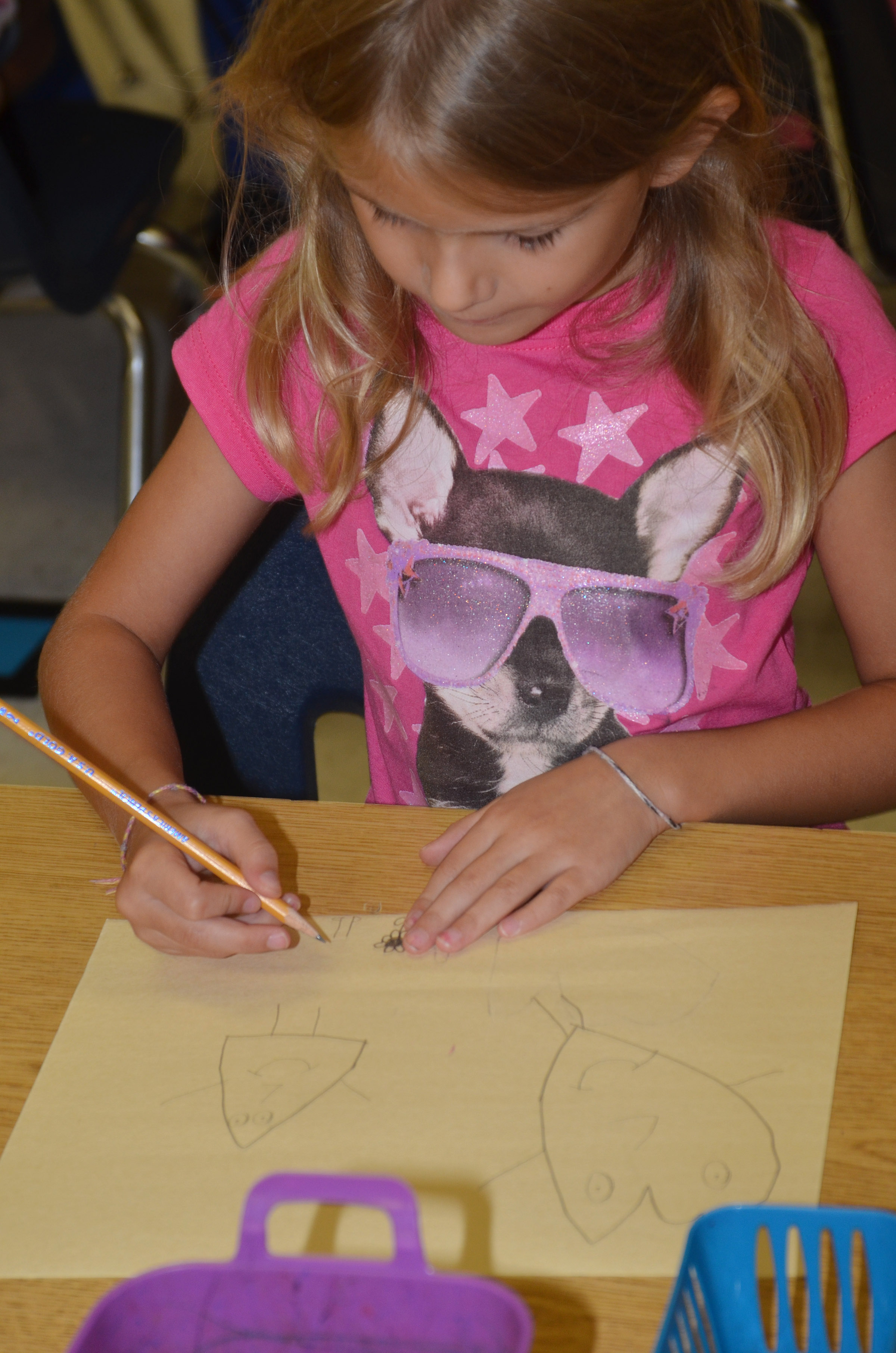 "CES first-grader Gracie Gebler draws her ""Beautiful Oops"" artwork."