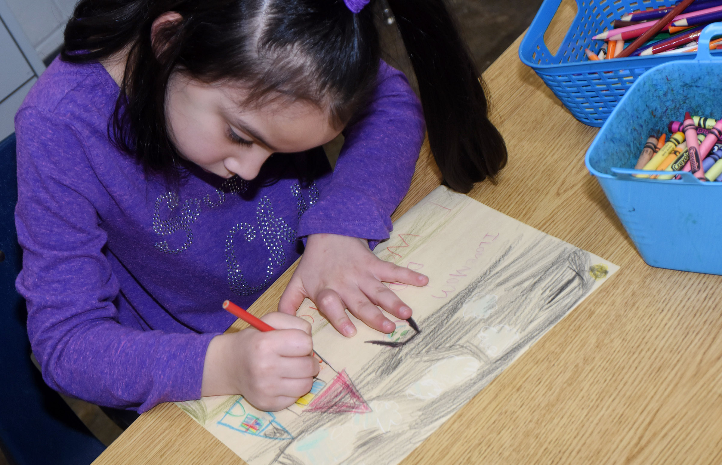 CES first-grader Nevaeh Agent draws her favorite Christmas present.