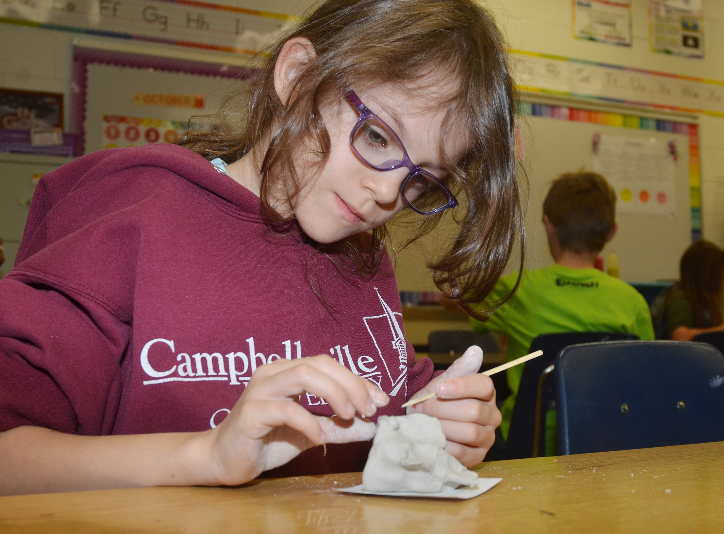 CES third-grader Lilly Wise adds eyes to her clay fish.
