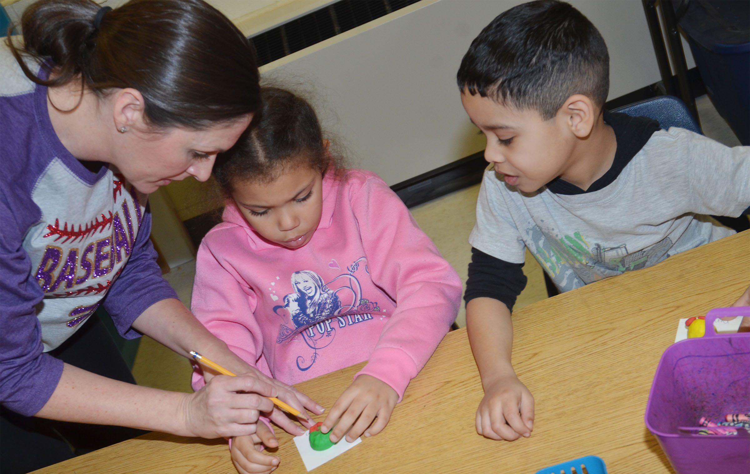 CES art teacher Adrienne Hash helps kindergarteners Jasymon Musselwhite, at left, with her owl as Demarcus Noyola watches.