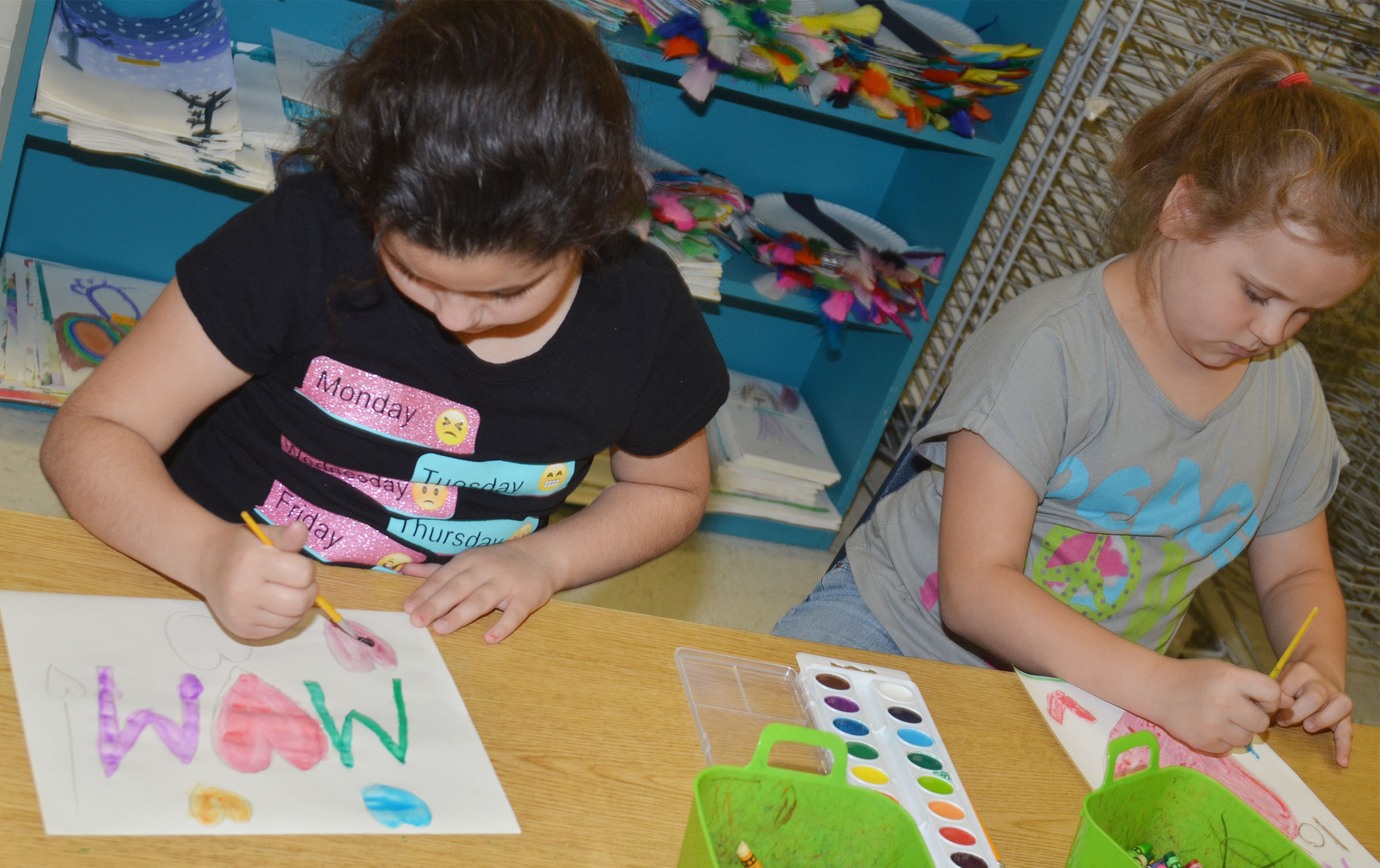 CES third-grader Brooklyn Boudreaux, at left, and Amaya Anguiano paint watercolor paintings for their mothers.