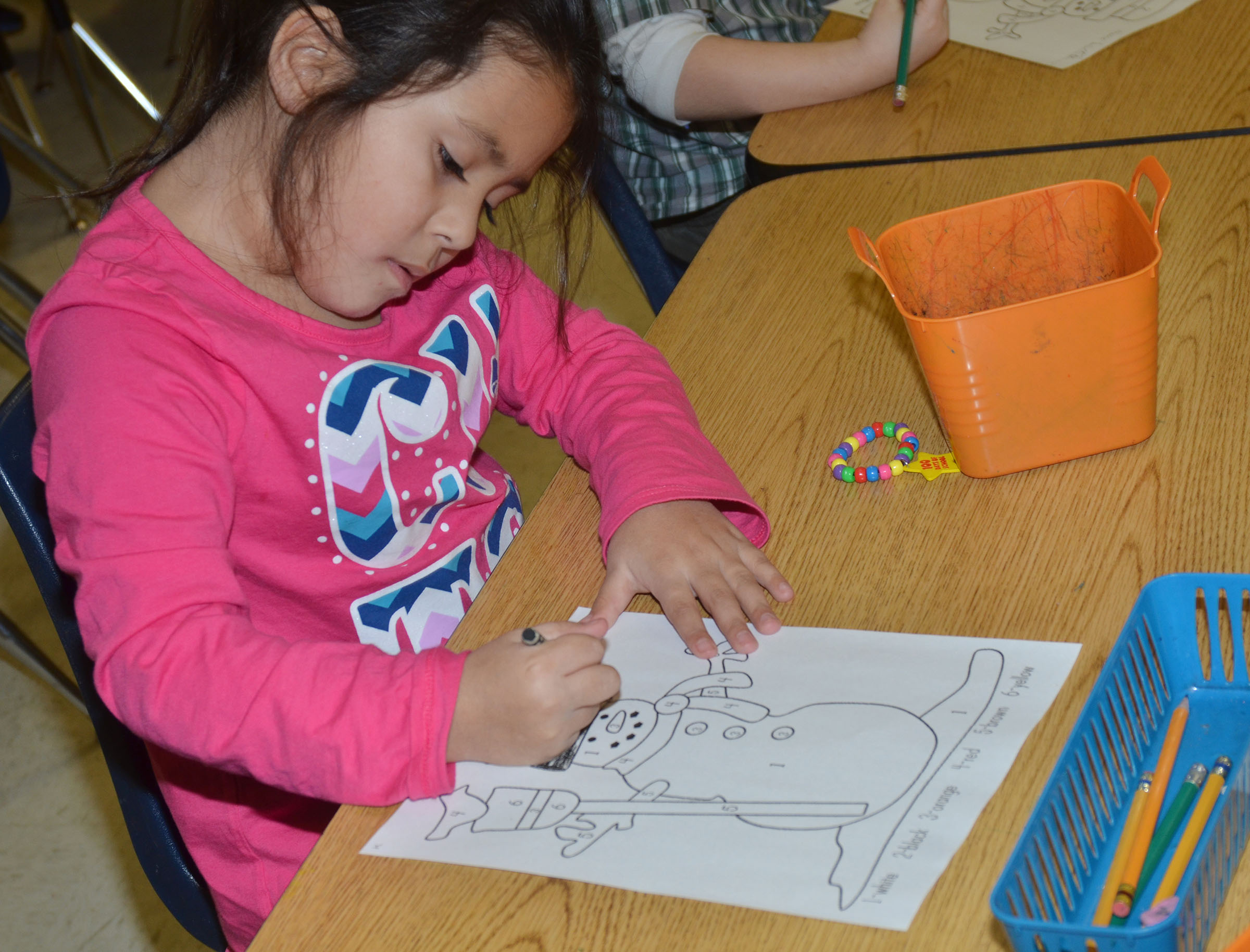 CES kindergartener Juliana Wolford colors her snowman for the coloring contest.