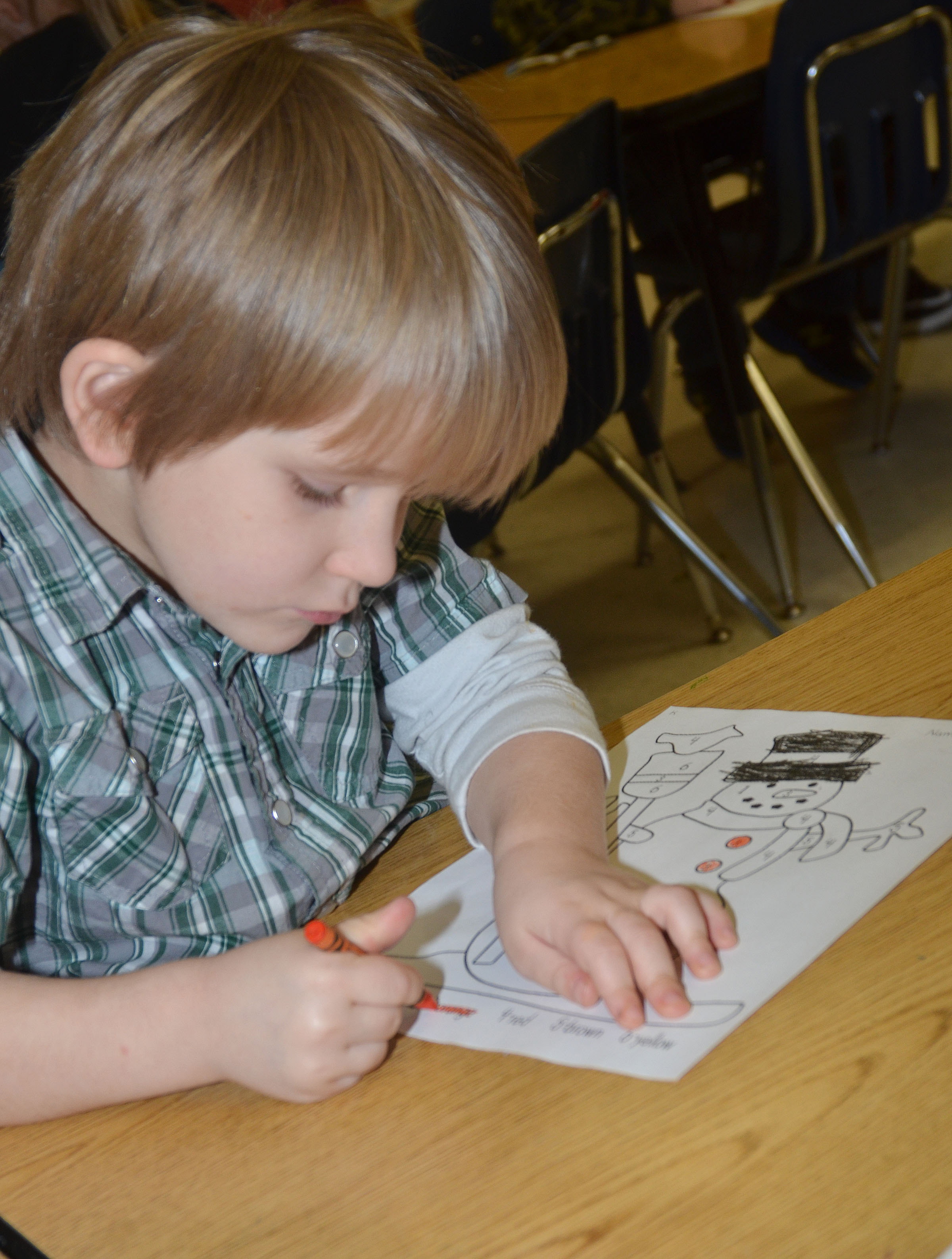 CES kindergartener Luke Banta colors his snowman for the coloring contest.