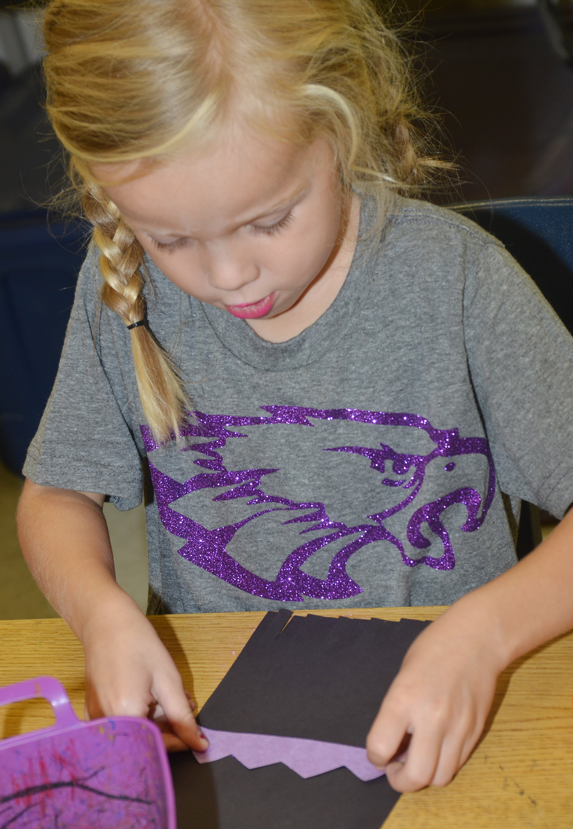 CES kindergartener Trinidy Gribbins glues a line on her magic carpet.