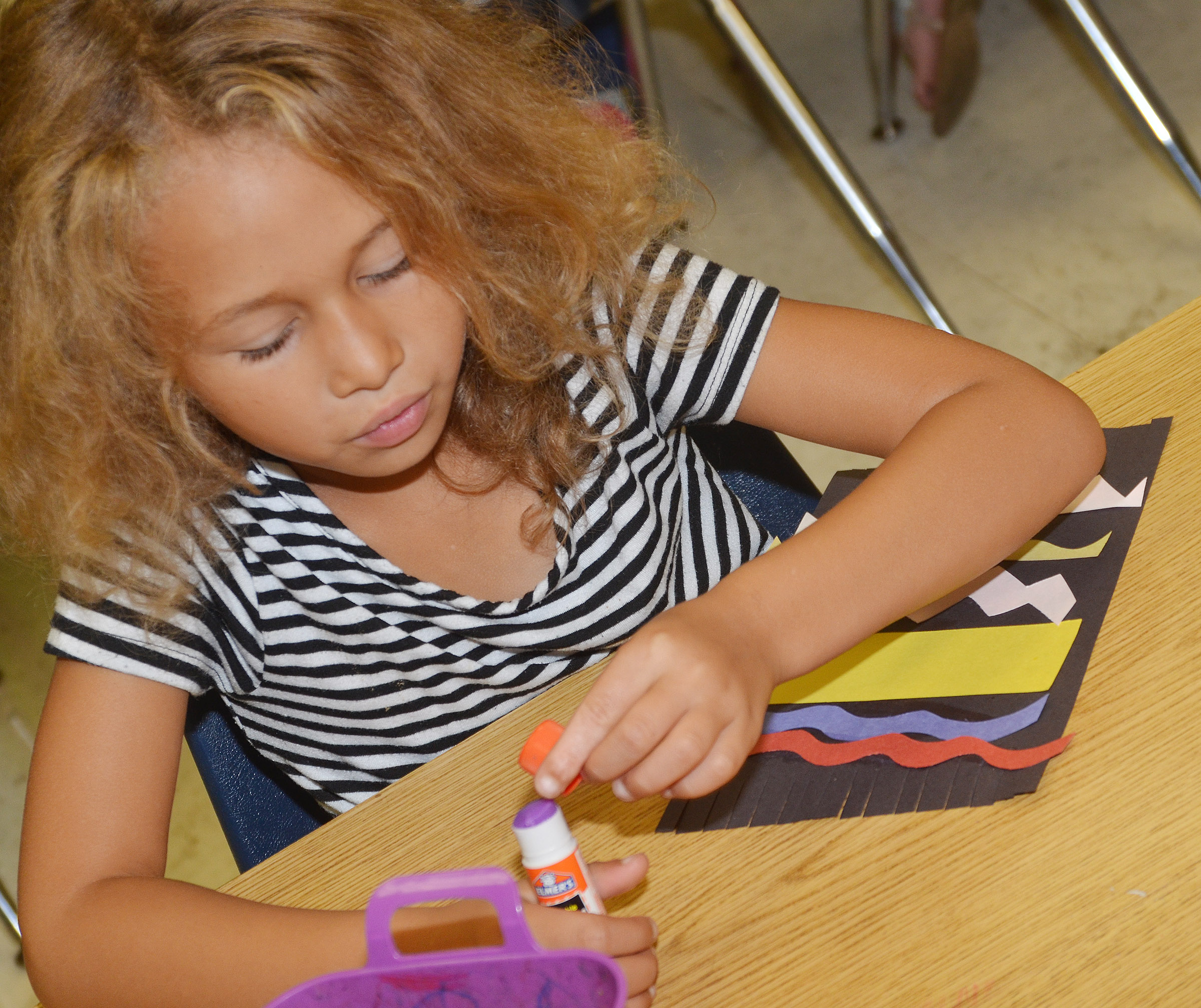 CES kindergartener Fallyn Smith glues lines on her carpet.
