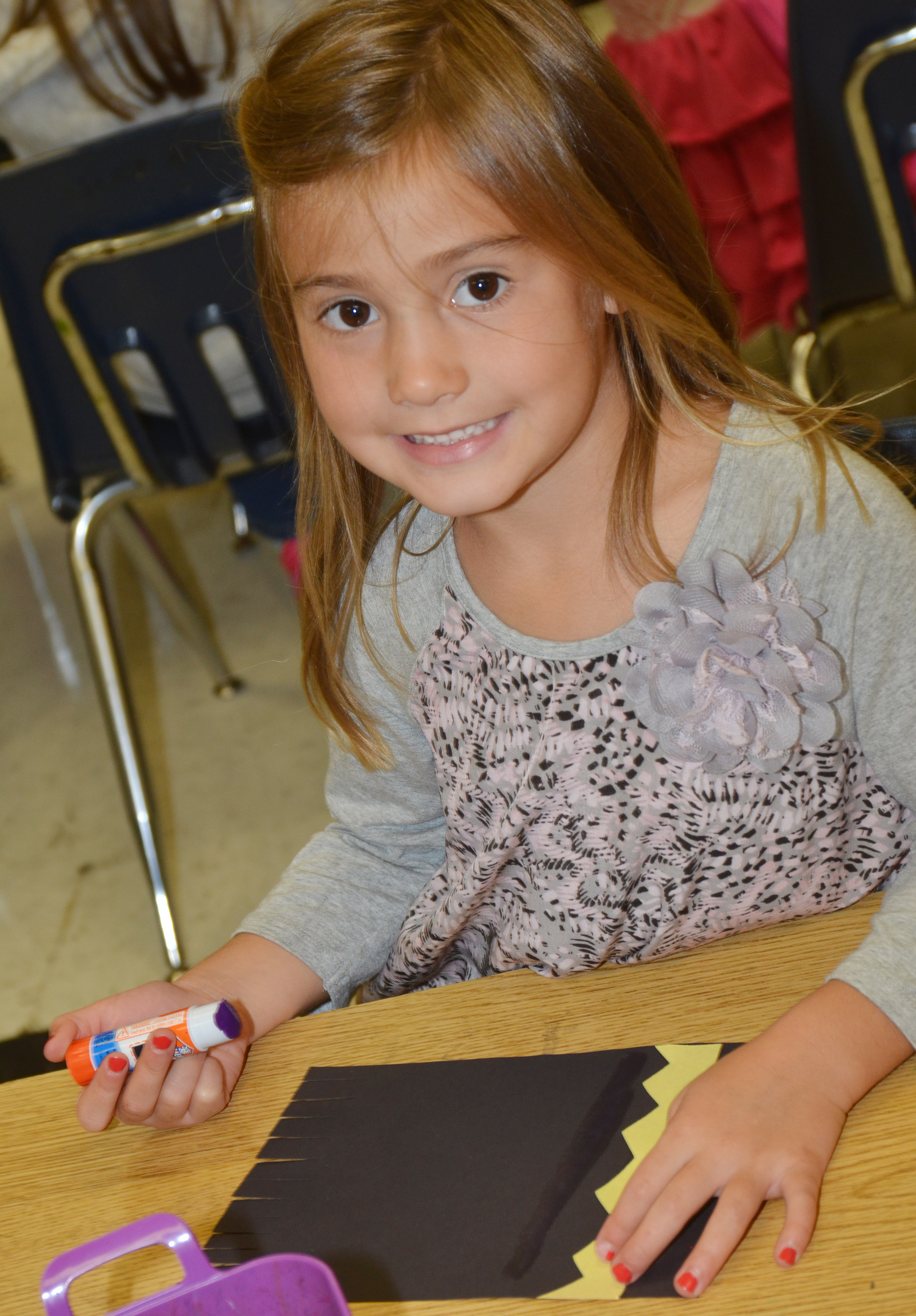 CES kindergartener Blakely Gray smiles as she glues together her magic carpet.