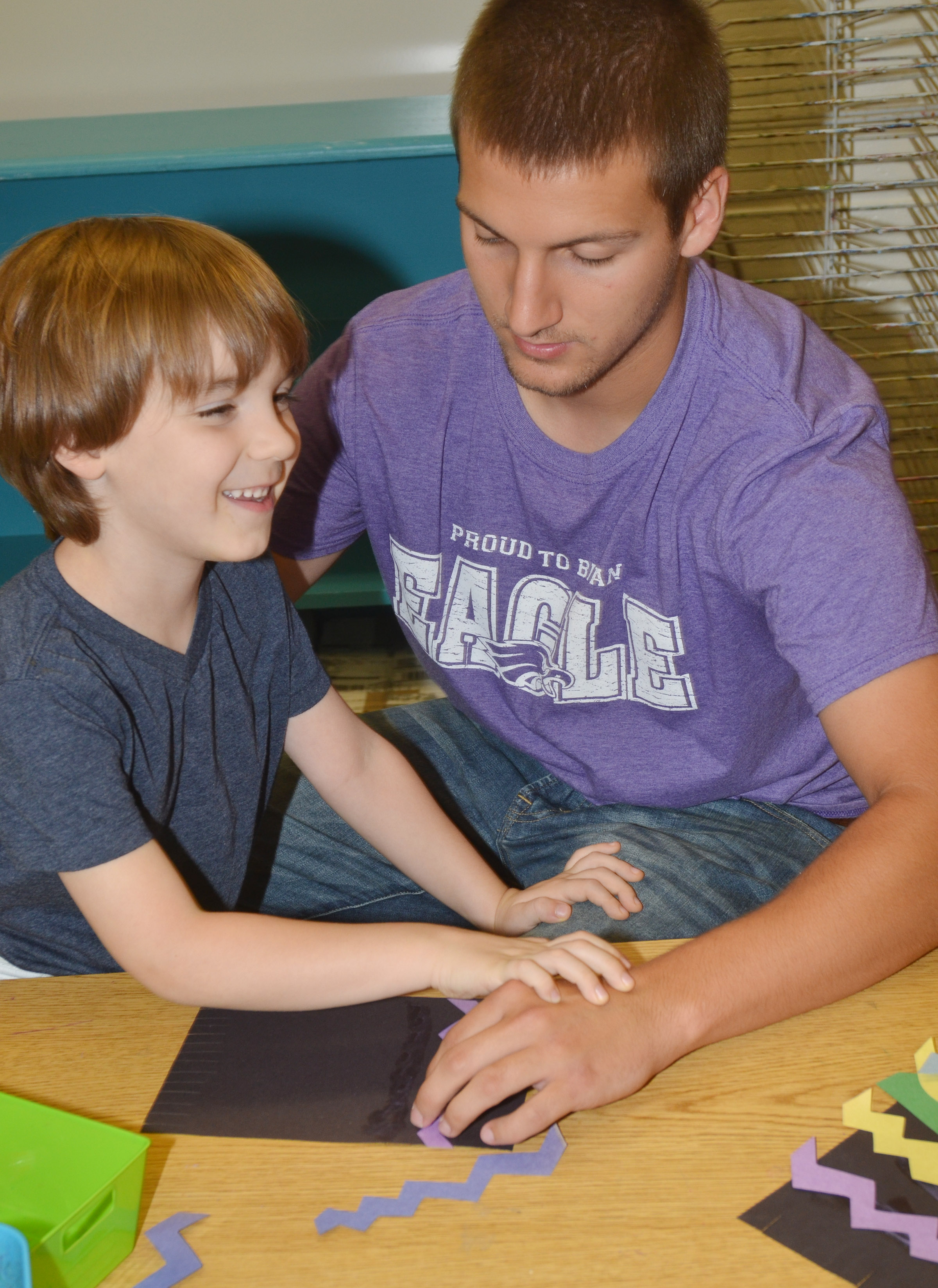 CES kindergartener Finley Williams makes his magic carpet, with help from instructional assistant Zach Durham.