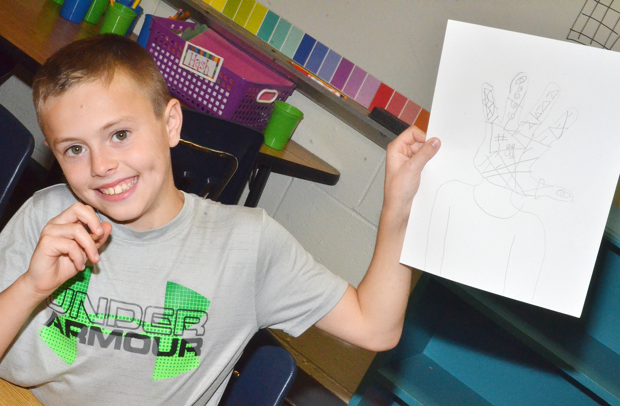 CES fourth-grader Keaton Hord holds his finished distorted self-portrait.