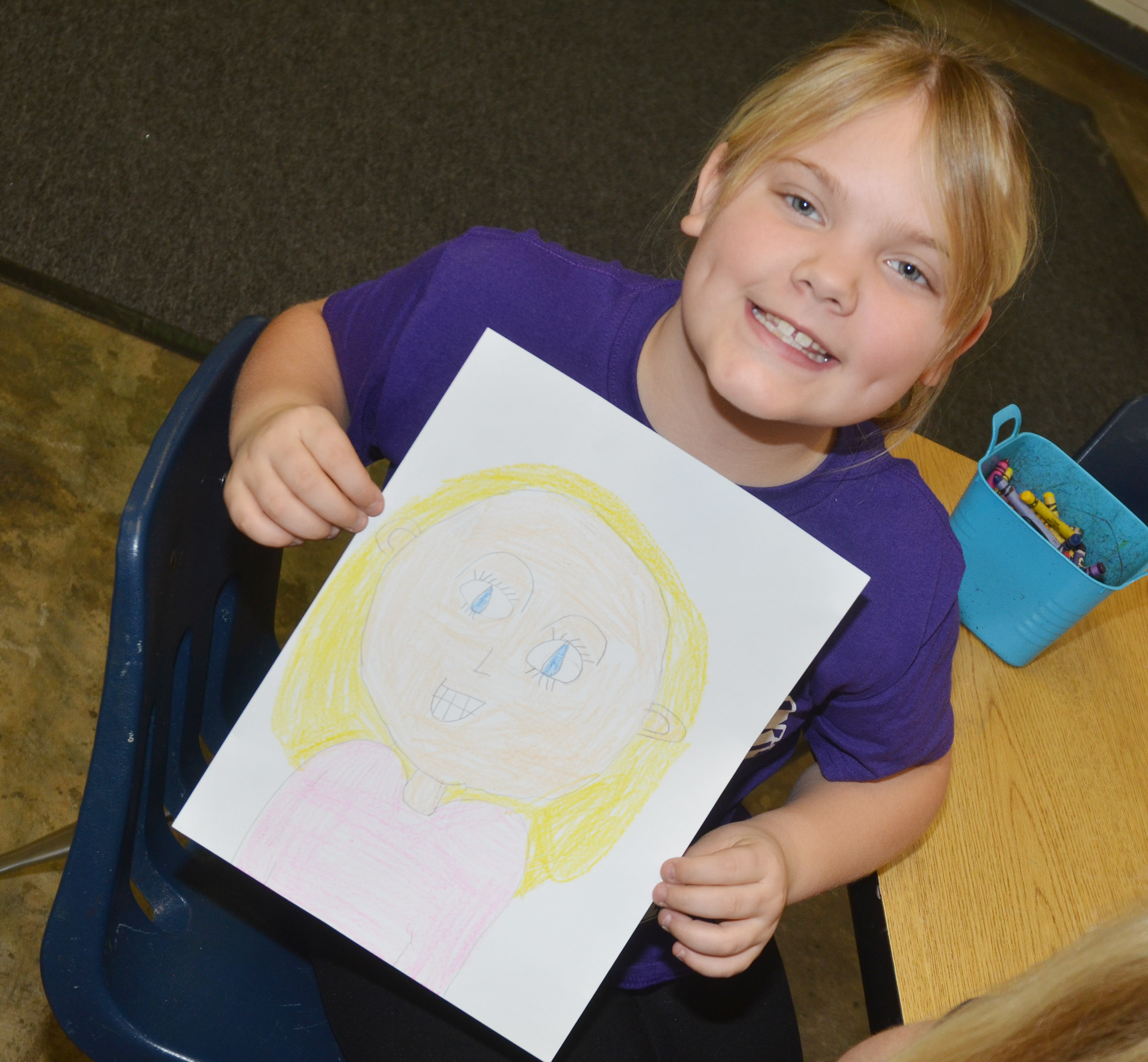CES second-grader Addysen England holds her finished self-portrait.