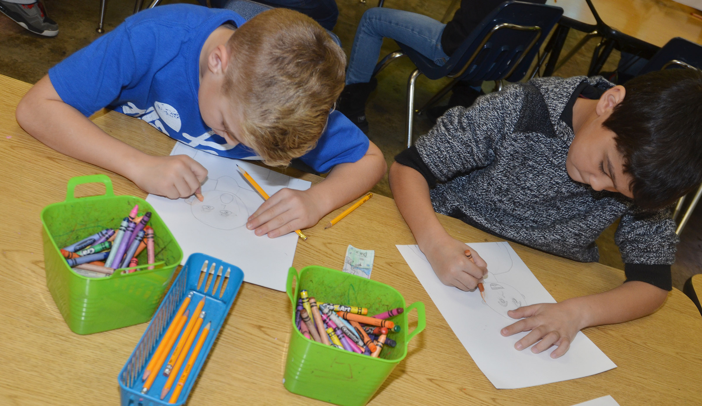 CES second-graders Dax Gray, at left, and Xadrian Fugate color their self-portraits.