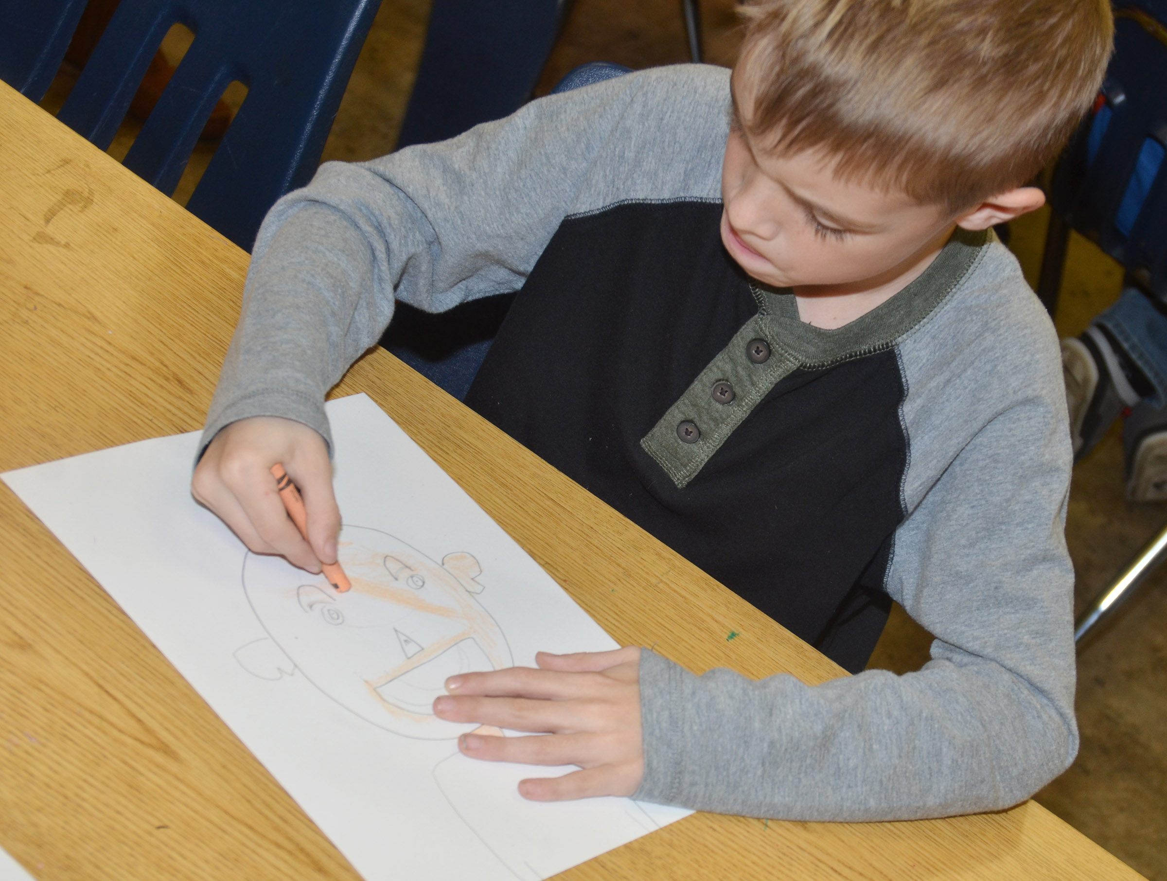 CES second-grader Logan Weddle colors his self-portrait.