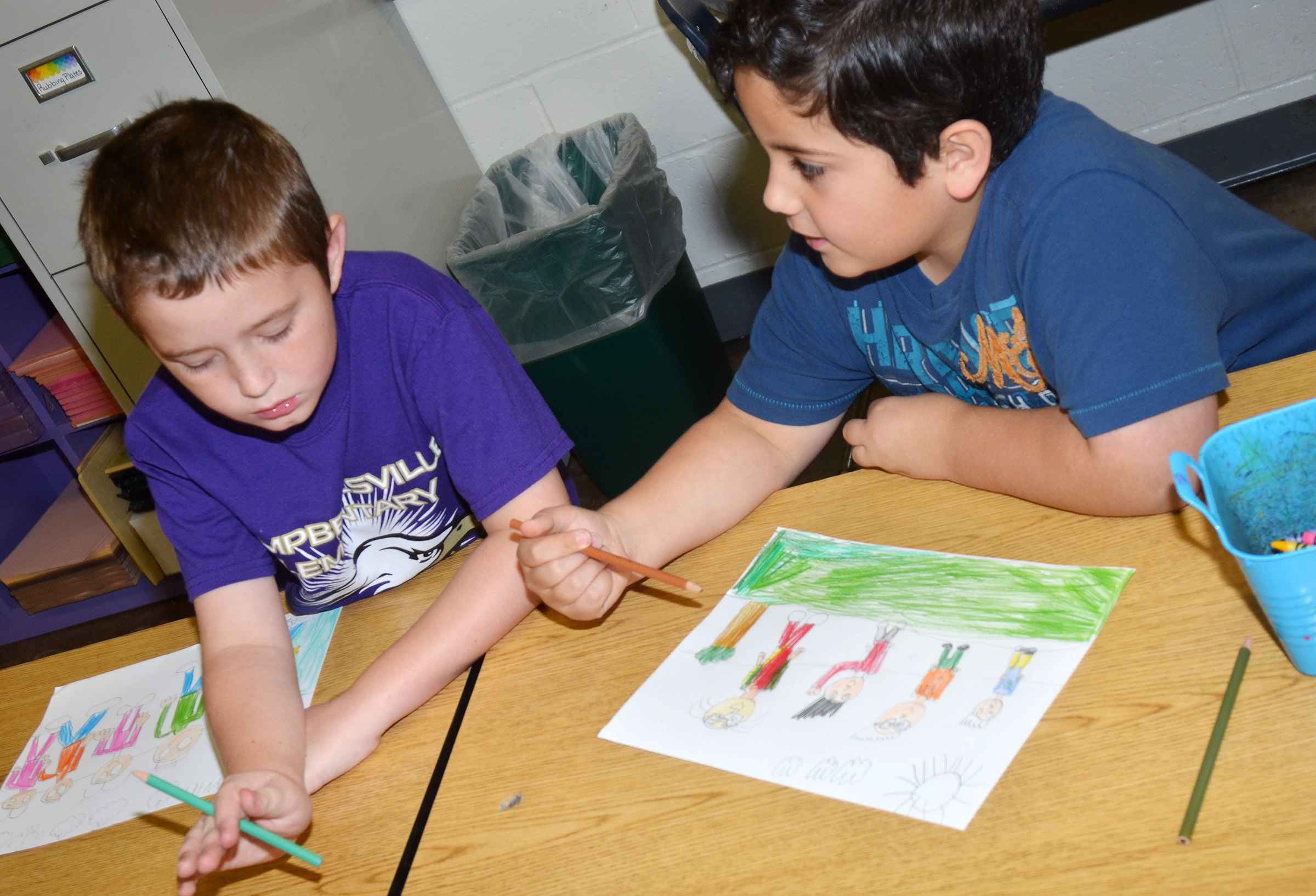 CES second-graders Kevin Bradfield, at left, and Nicholas Almeida talk as they color their family portraits.