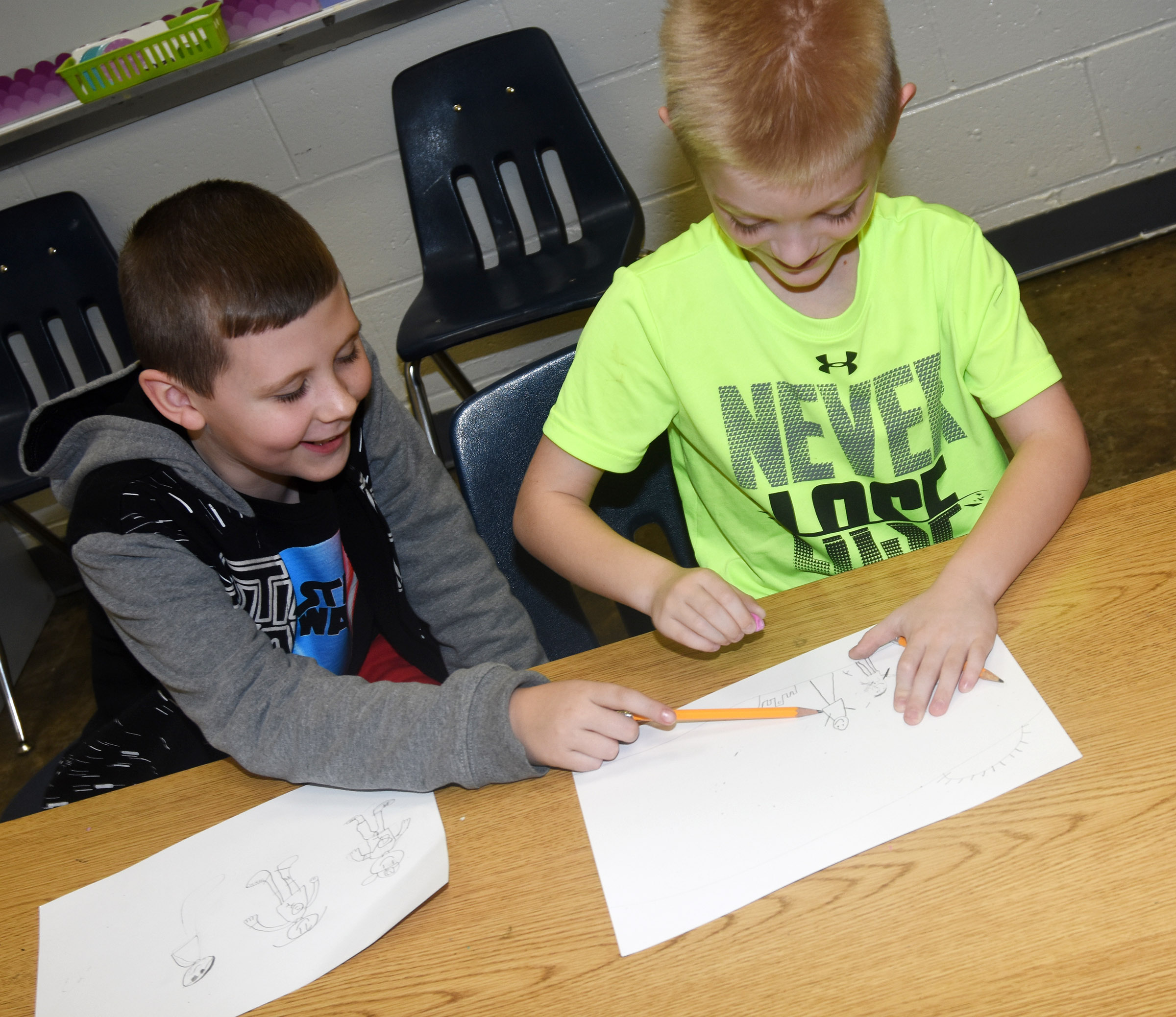 CES third-graders Ryan Tungate, at left, and Evan Cundiff talk as they draw their family scenes.