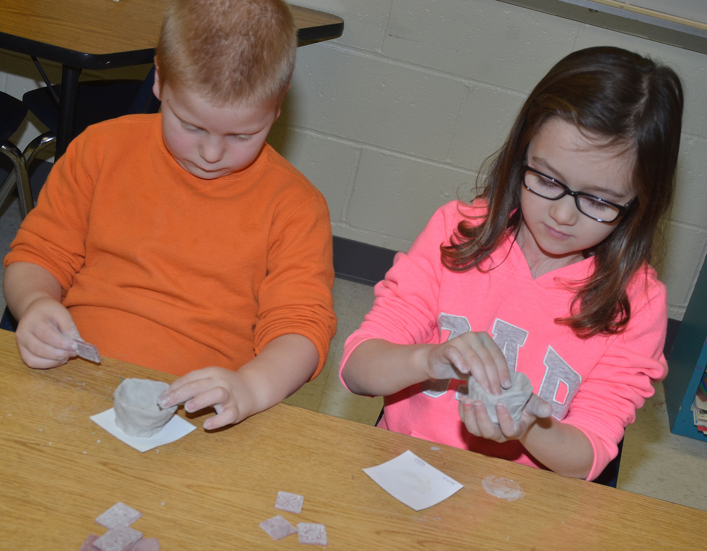 CES first-graders Ben Parrott, at left, and Anna Keith shape their pots.