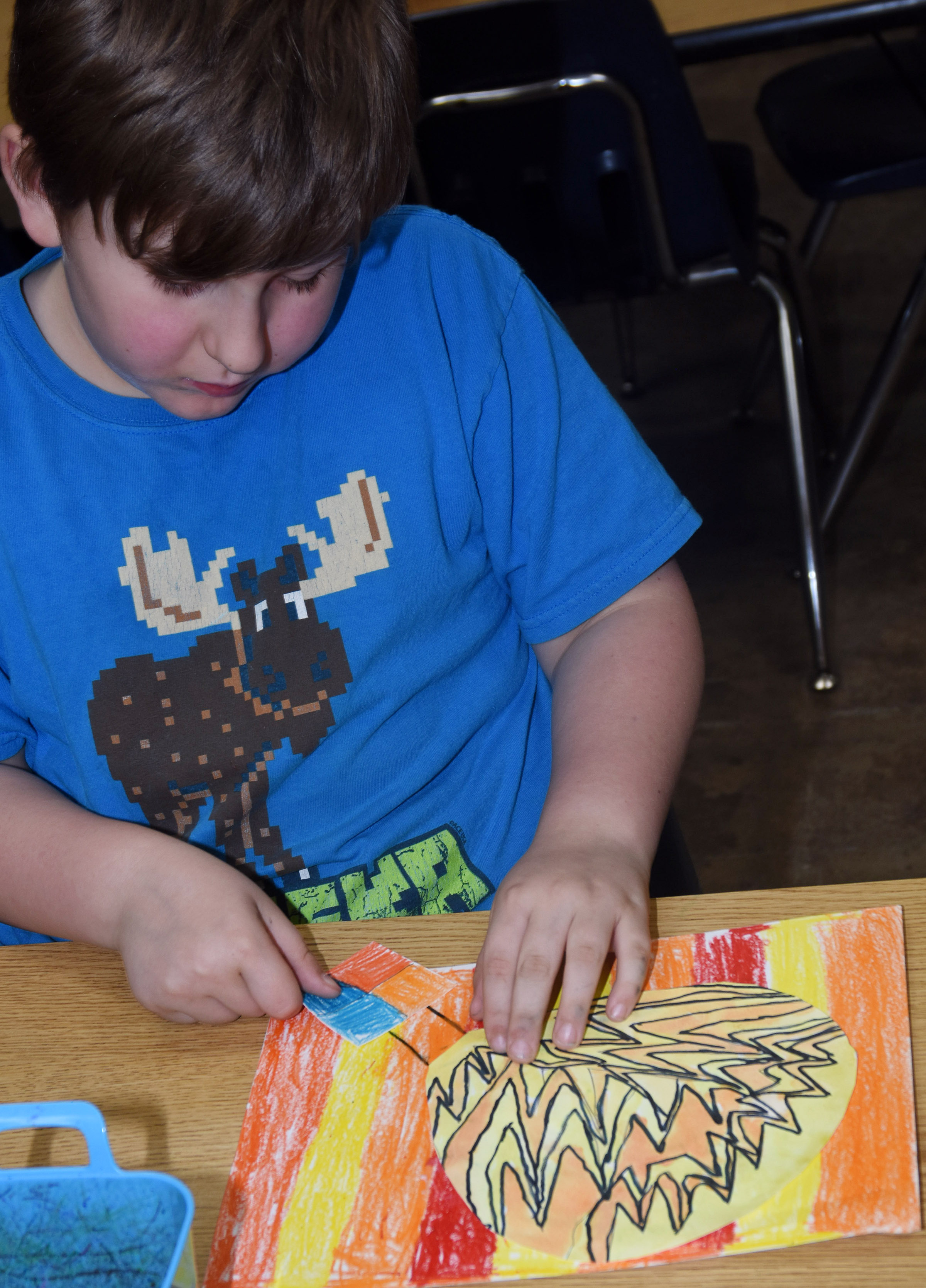 CES second-grader Tommy Caswell glues his hot air balloon to his background.