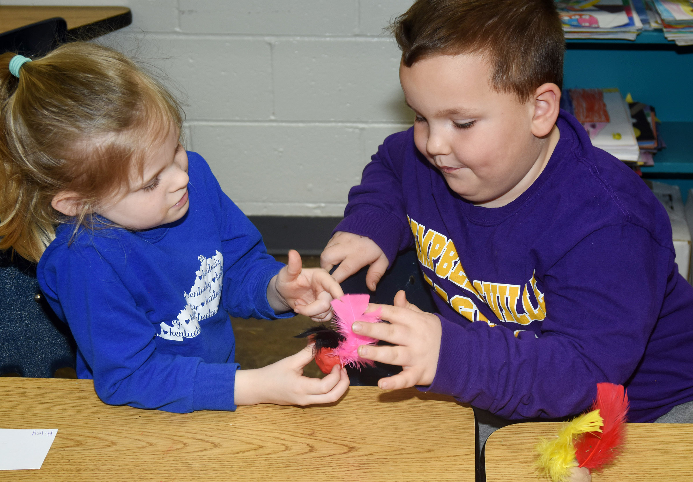 CES kindergarteners Riley Bright, at left, and Mason Gribbin look at each other's owl sculptures.