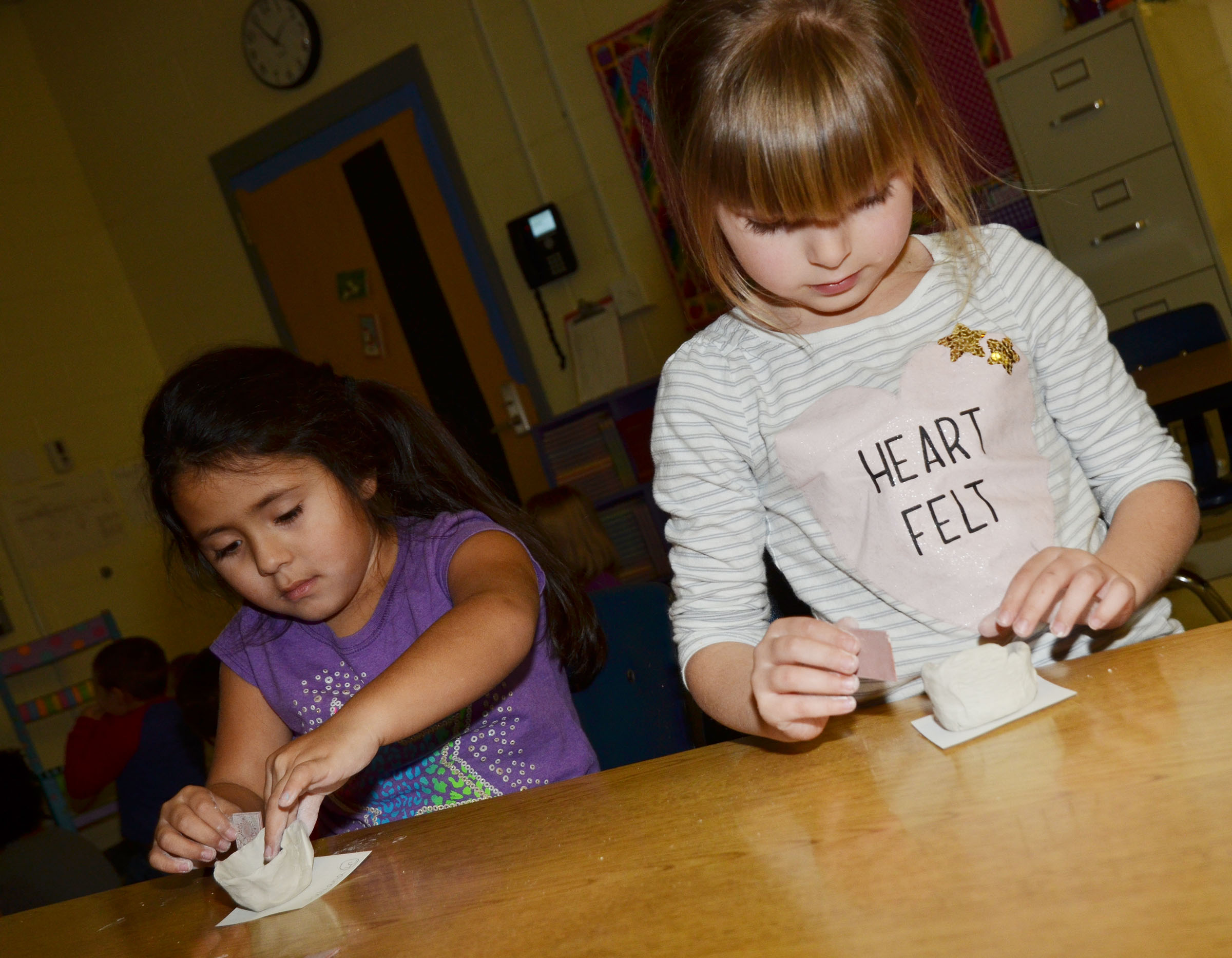 CES kindergarteners Juliana Wolford, at left, and Madison Wilhoite form their pinch pots.