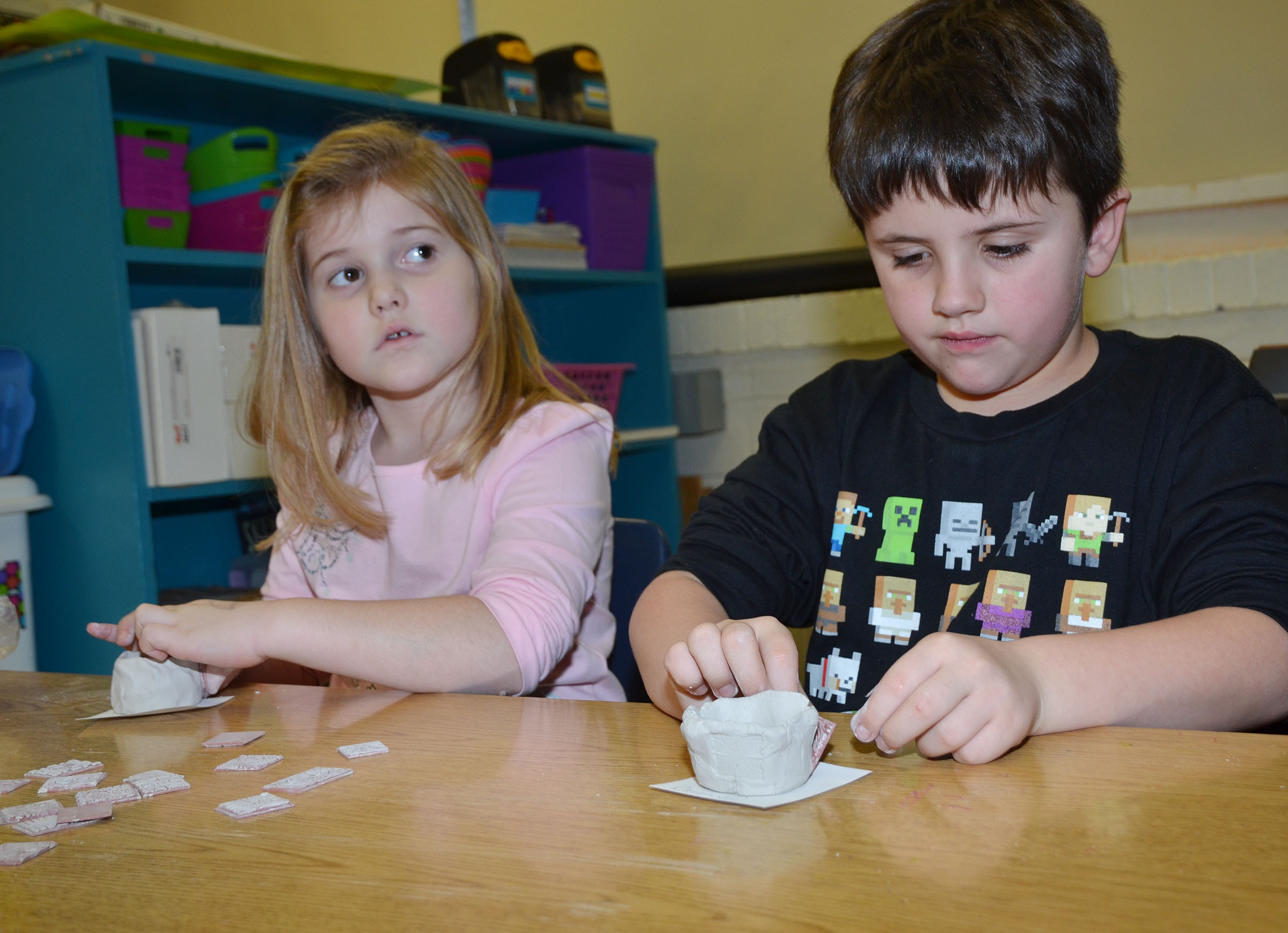 CES kindergarteners Aubreigh Knifley, at left, and Casen Meredith add designs to their pinch pots.